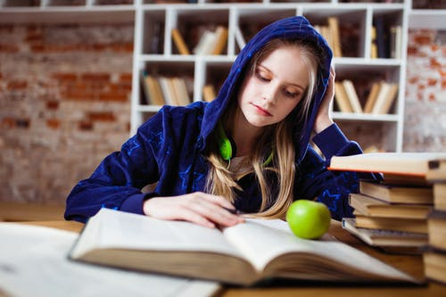 Woman Wearing Blue Jacket Sitting on Chair Near Table Reading Books