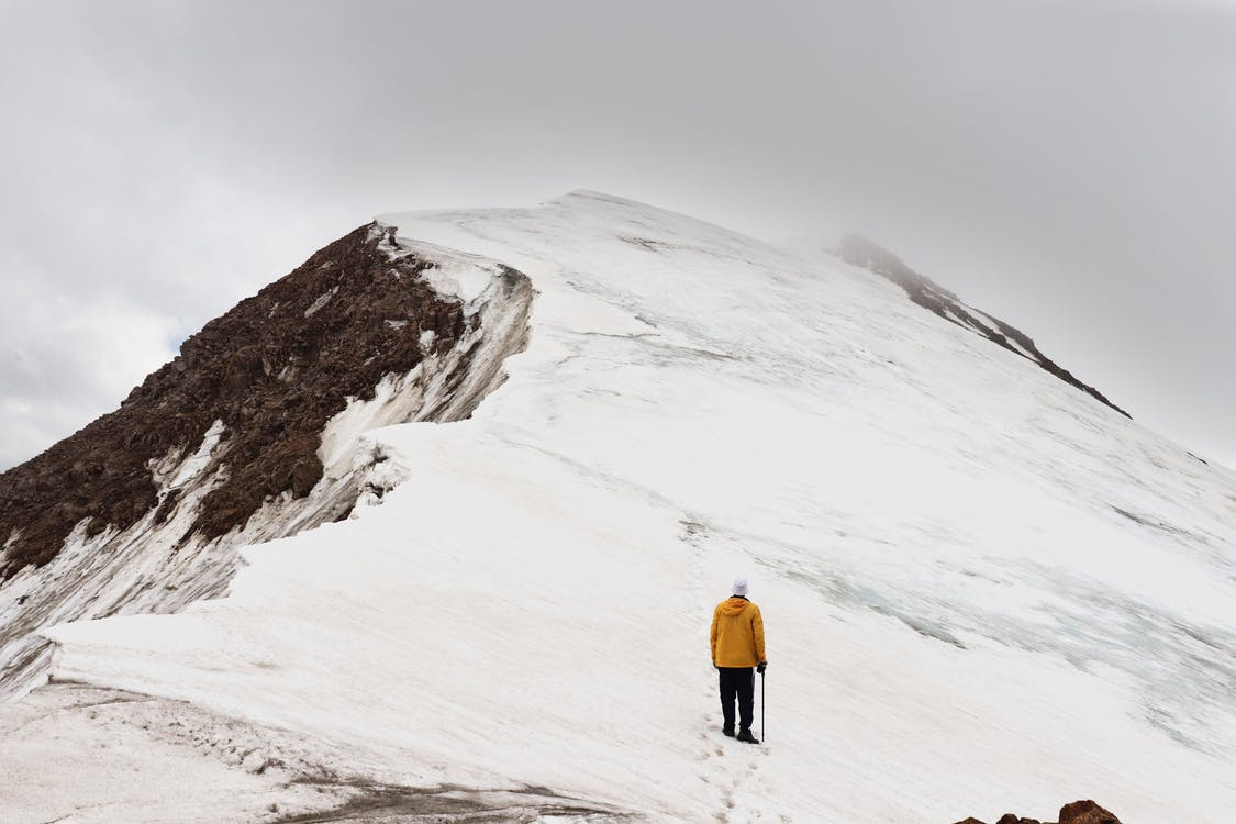 Man Climbing Snow Covered Hill