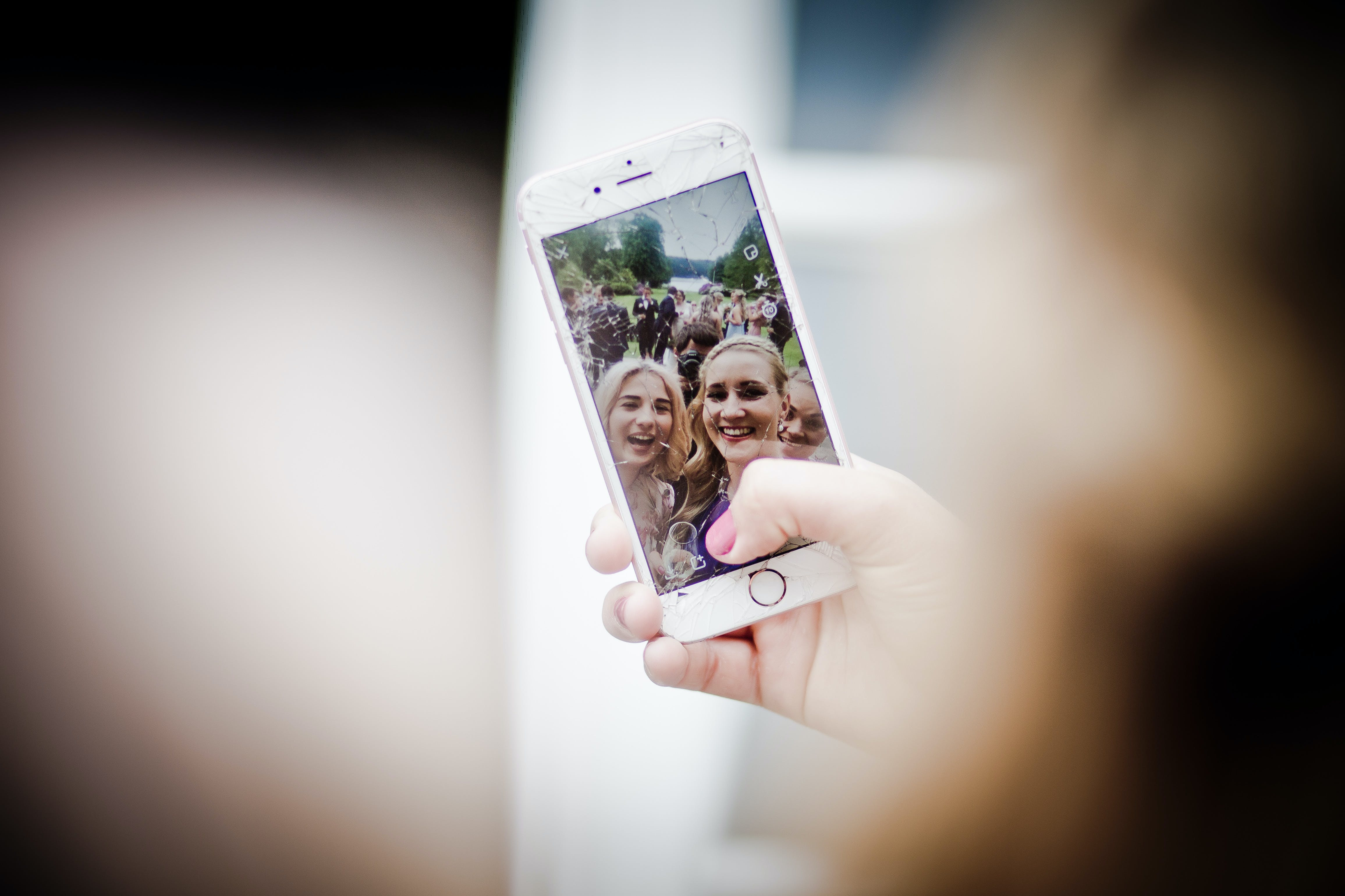 Selective Focus Photo of Gold Iphone 6 Displaying Two Women Taking Selfie