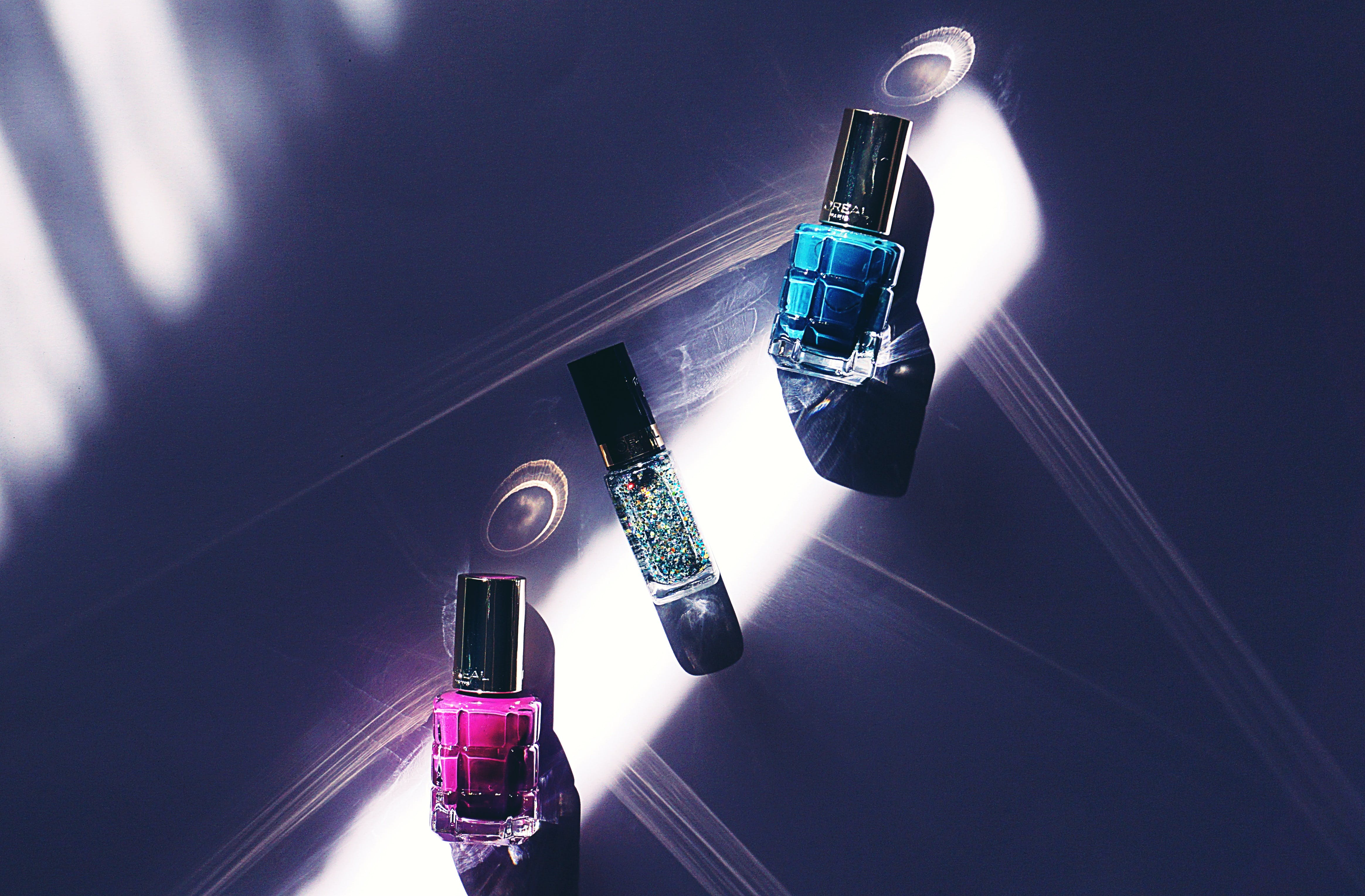 Three Assorted-color Nail Polish Bottles on Surface
