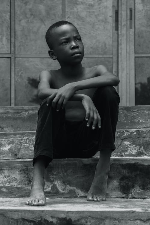 Grayscale Photo of Boy Sitting on Stair