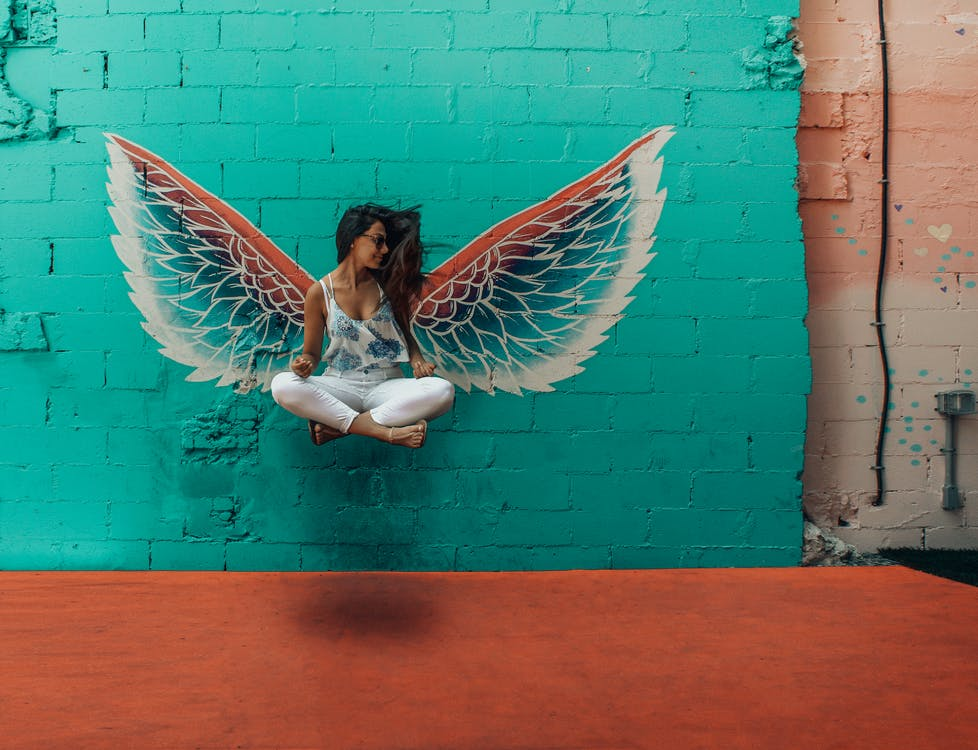 Woman Taking Picture Beside Wings Decor