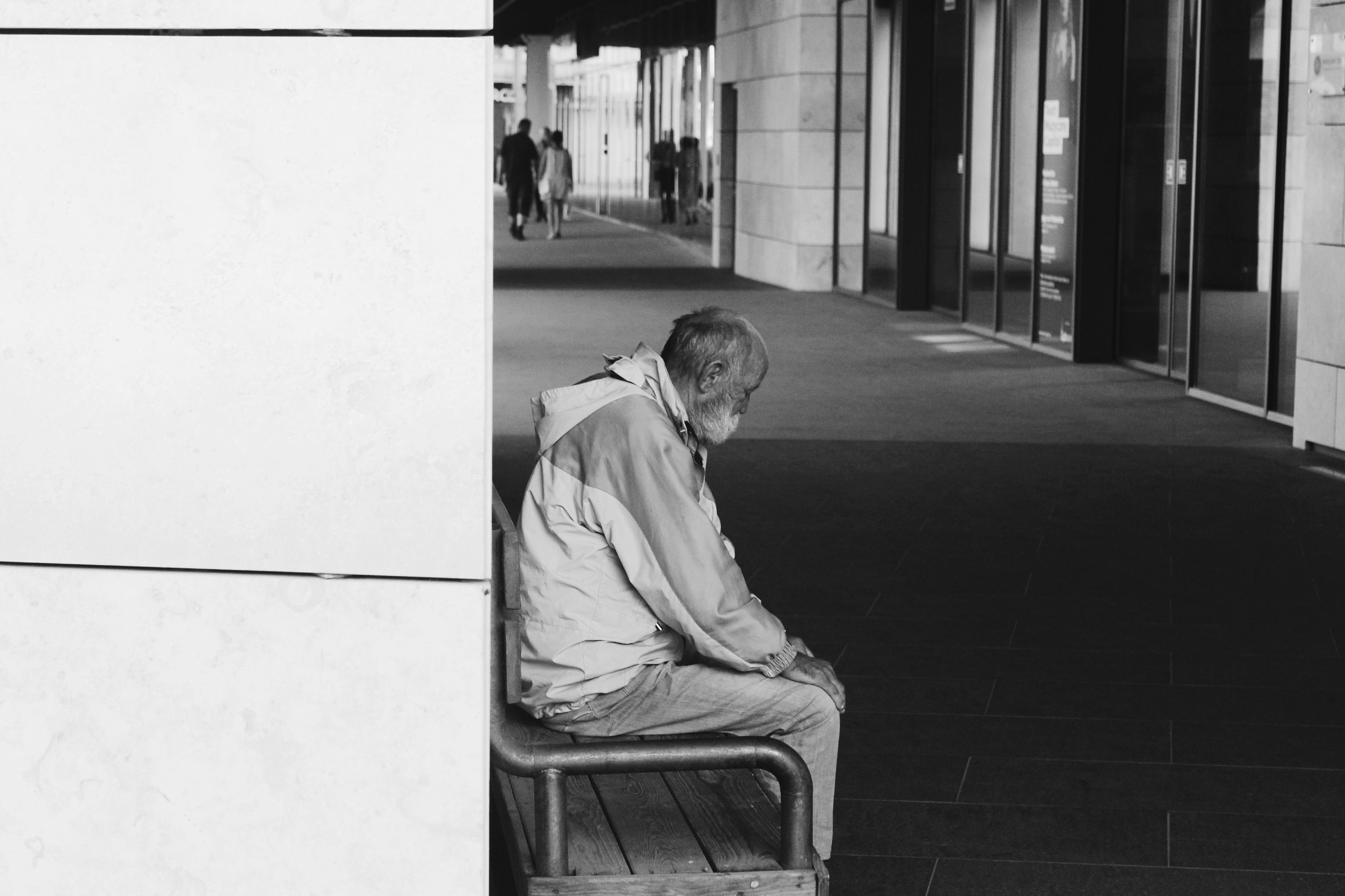 Grayscale Photography of Man Sitting on Chair