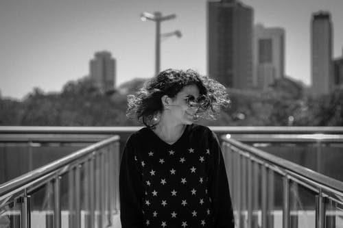 Grayscale Photo of Smiling Woman Wearing Star-print Long-sleeved Shirt Standing Between Metal Railings