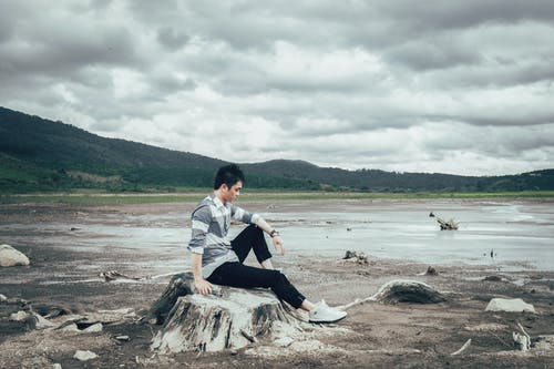 Man Sitting on Tree Stump Near Body of Water