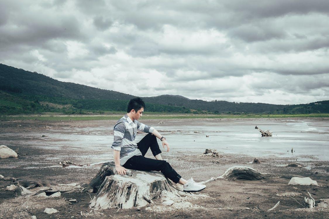 Man Sitting on Tree Stump Near Body of Water