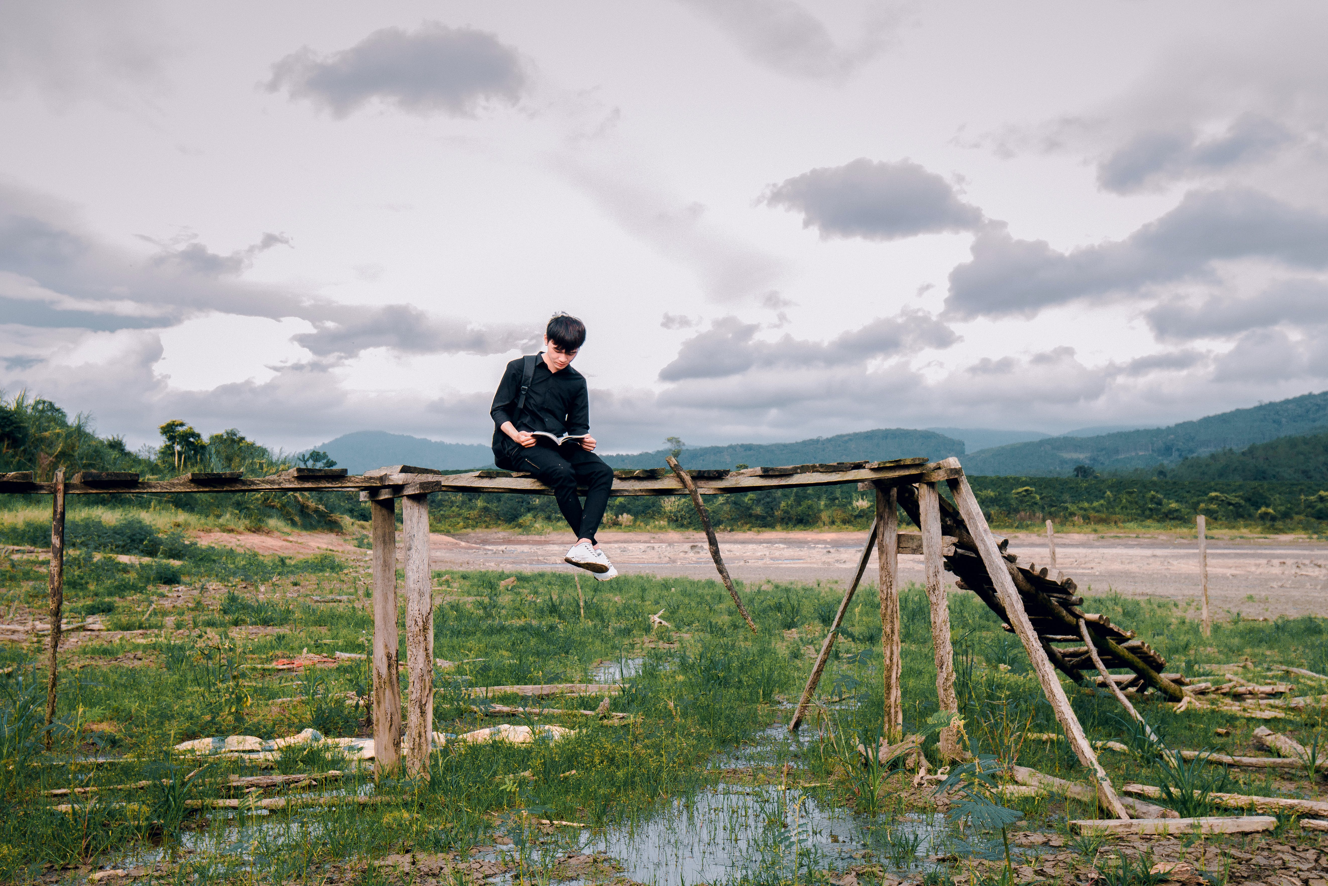 Man Sitting on Brown Wooden Bridge