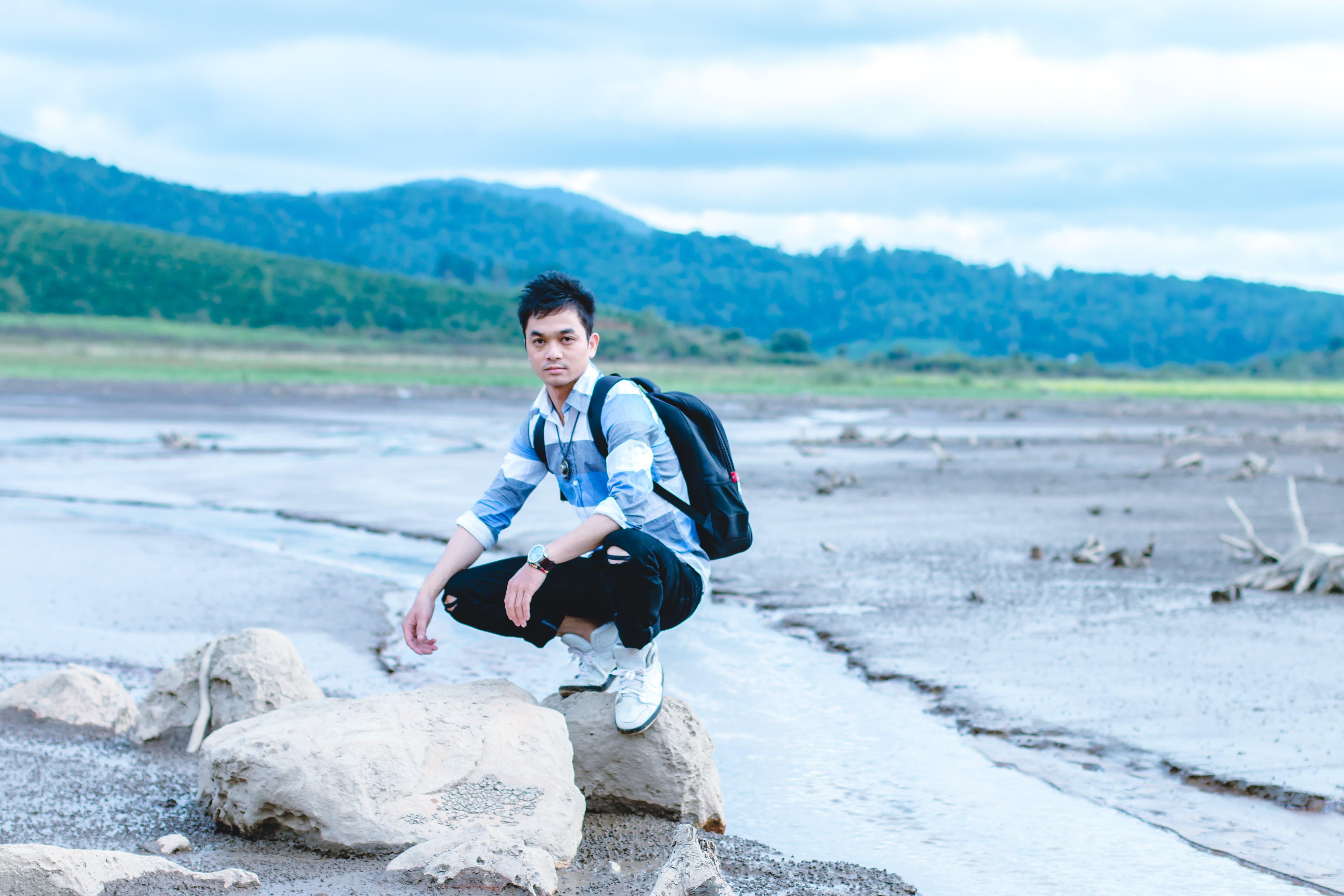 Man on Gray Rock Beside Body of Water