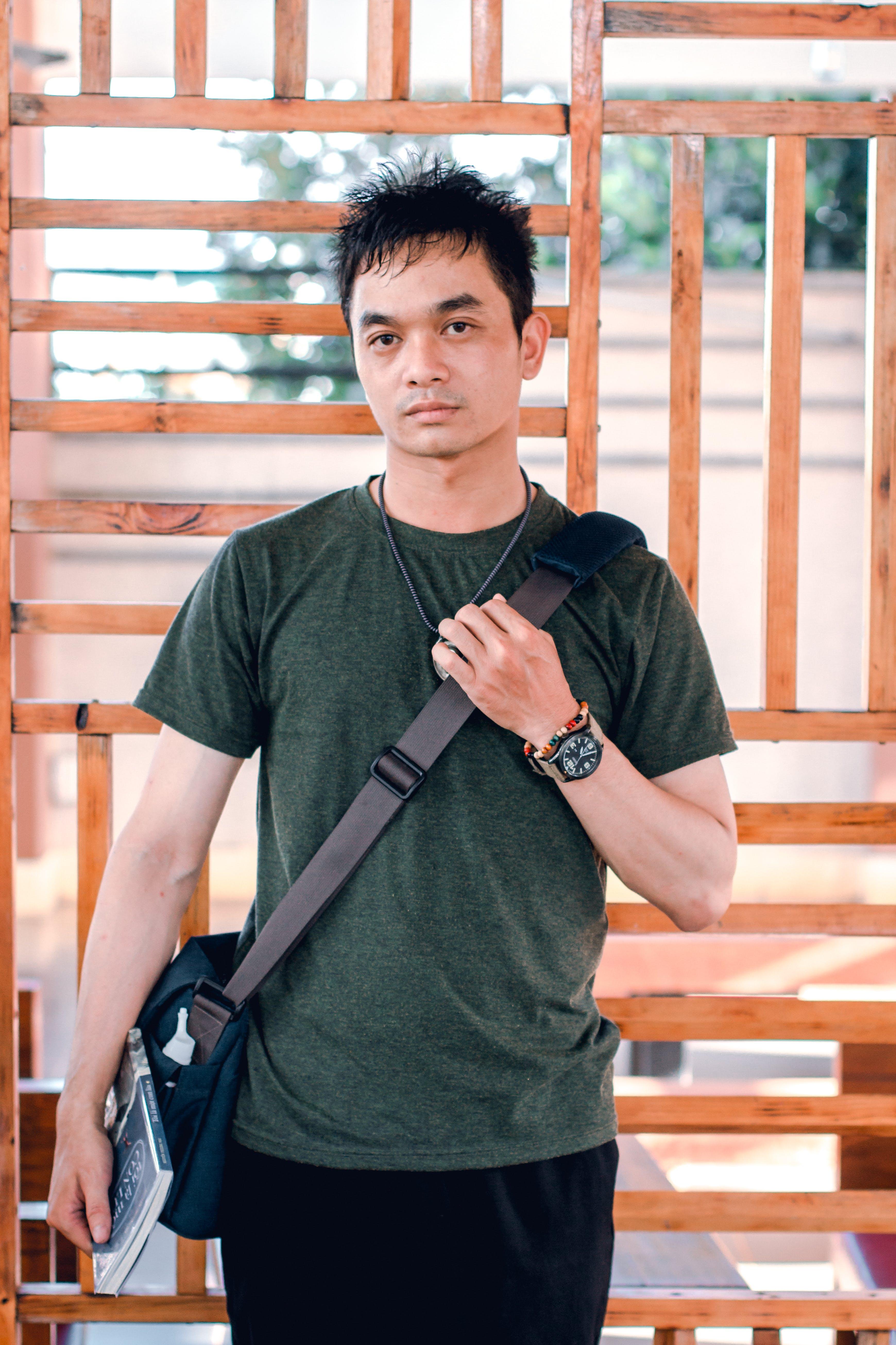 Man Holding Crossbody Bag Standing on Outdoors