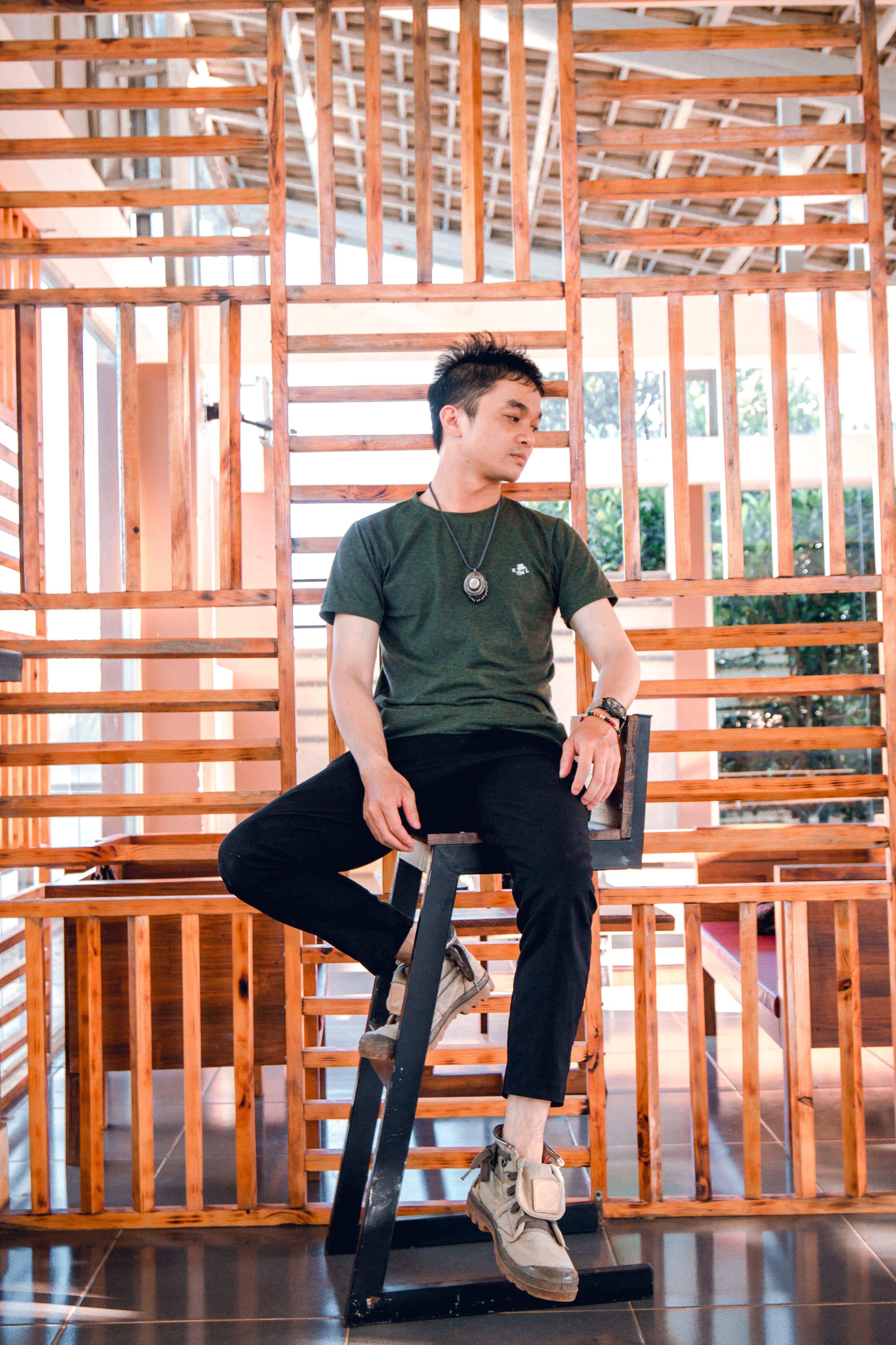 Man in Green Crew-neck Shirt Sitting on Black Wooden Chair