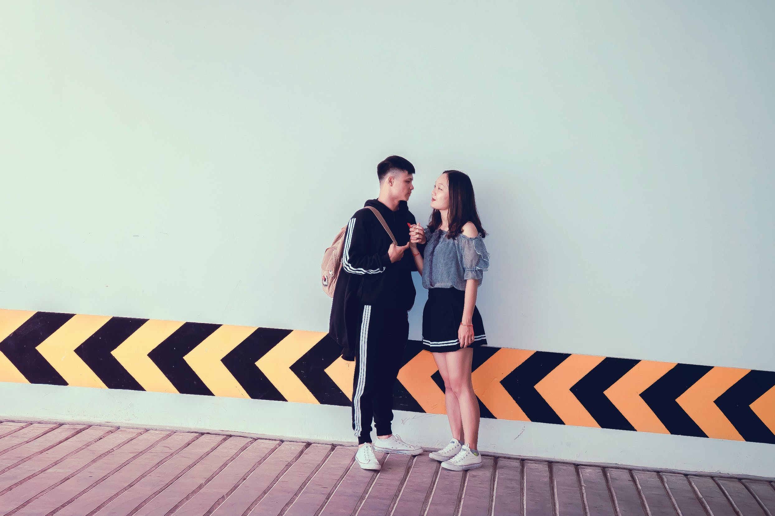 Man and Woman Looking at Each Other Near Wall