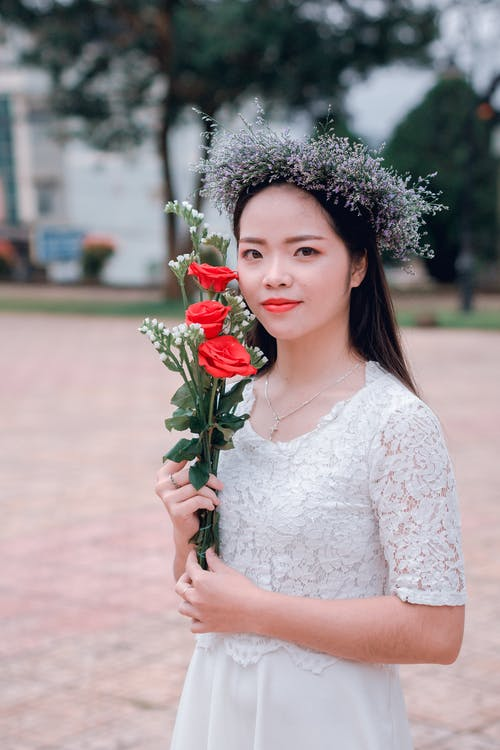 Selective Focus Photography of Woman Holding Three Red Rose Flowers