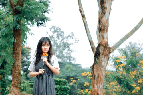 Woman Holding Orange Flower While Standing Outdoors