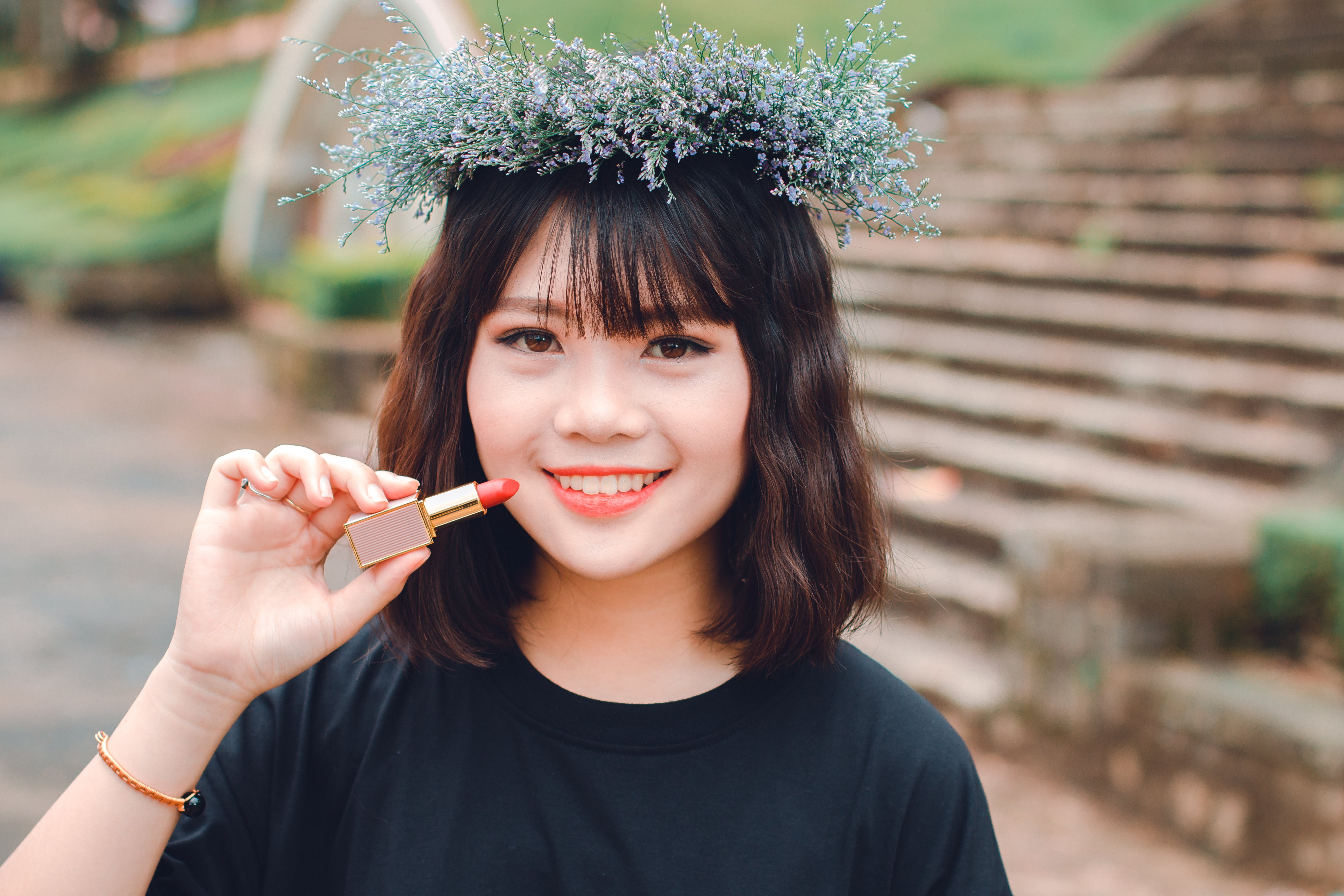 Woman Smiling While Holding Lipstick