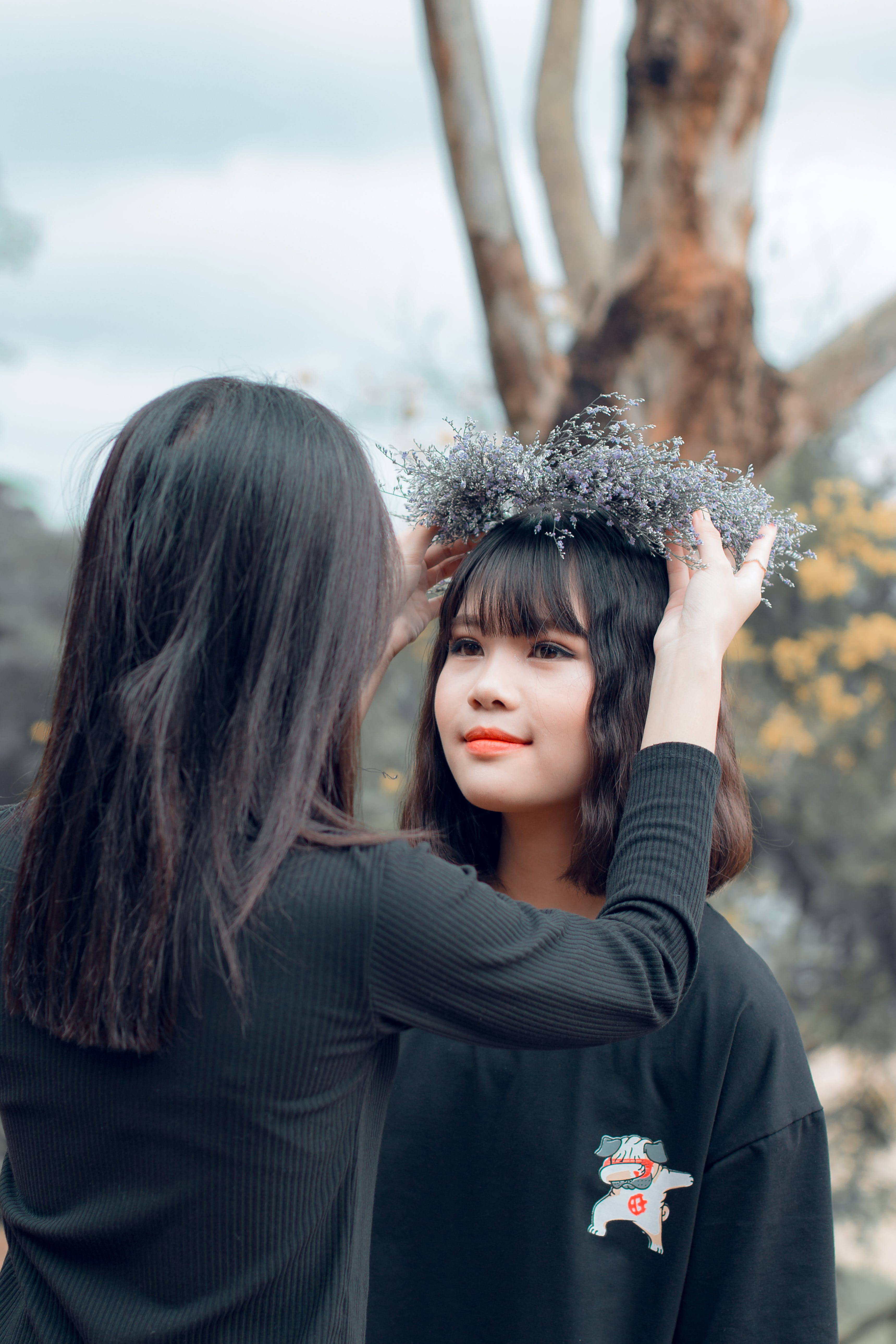 Woman Putting Crown on Women's Head