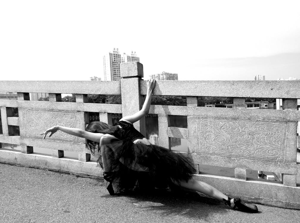 Ballerina Performing Beside Safety Fence Grayscale Photo