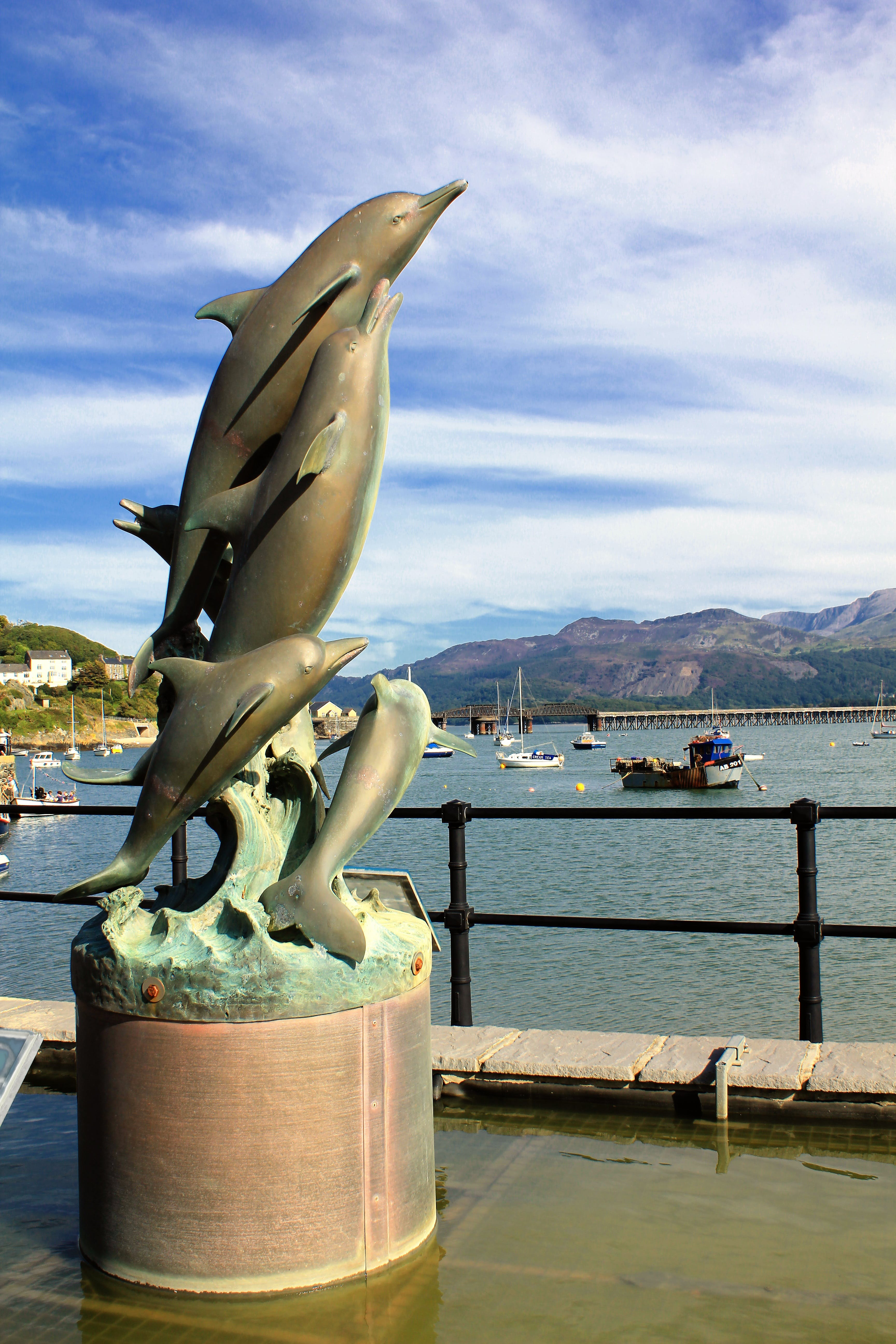 Four Gray Dolphins Statue Near Water