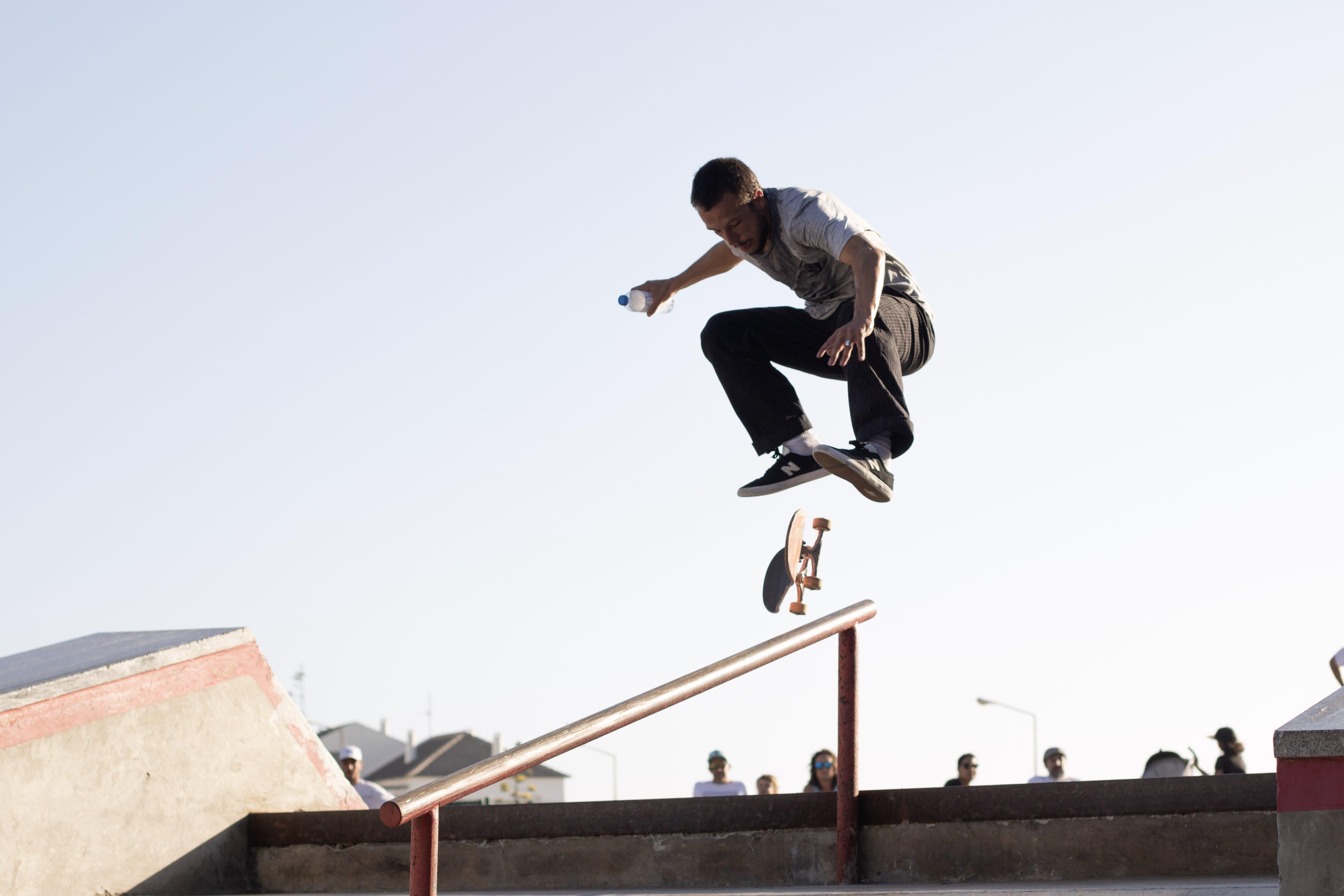 Man Wearing White T-shirt Performing Skateboard Tricks on Rail Under Blue Sky