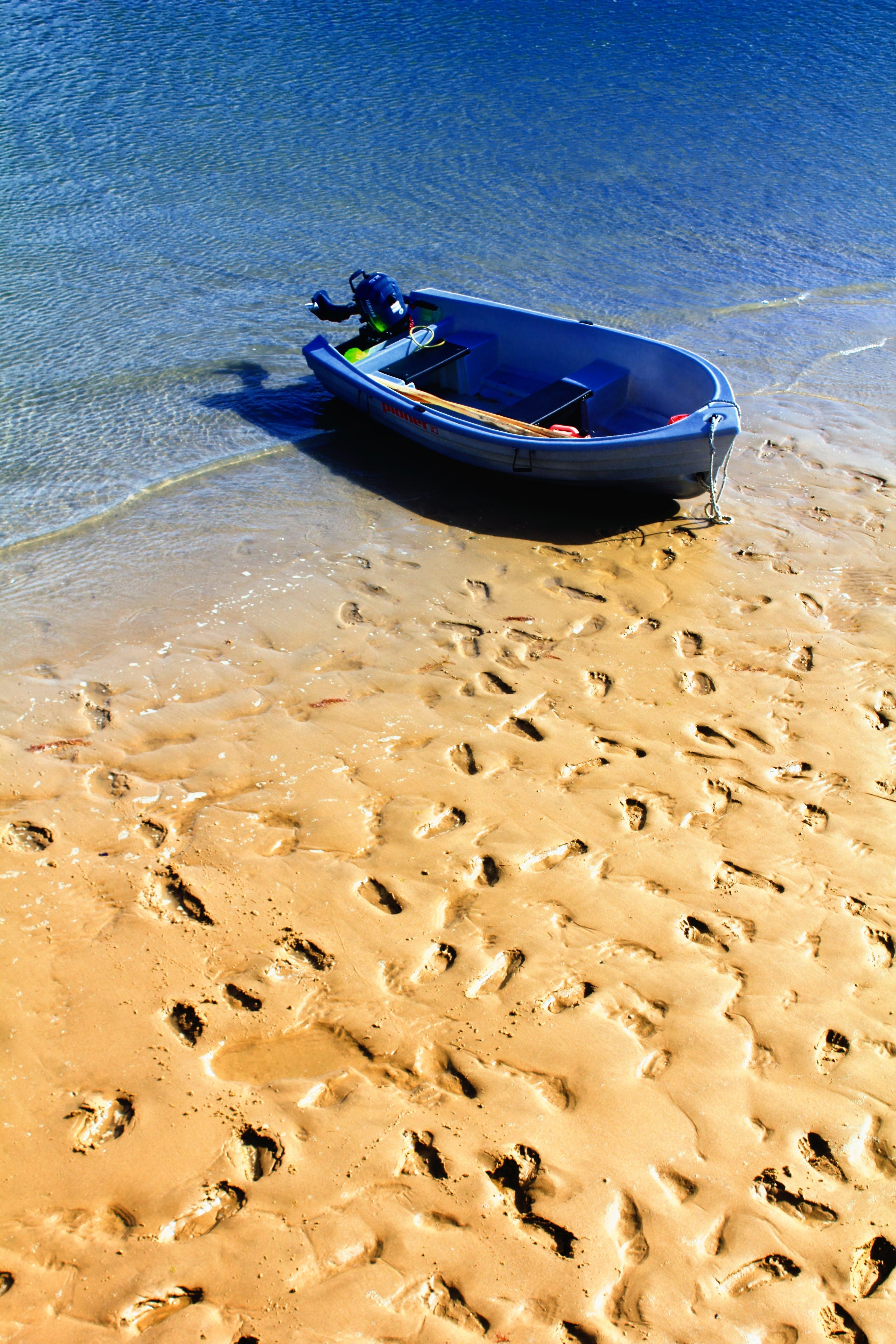 Blue Outboard Boat on Seashore