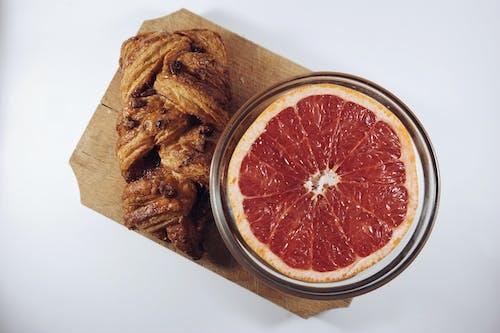 Sliced Orange Fruit in Glass Bowl Beside Baked Bread Both on Brown Wooden Board