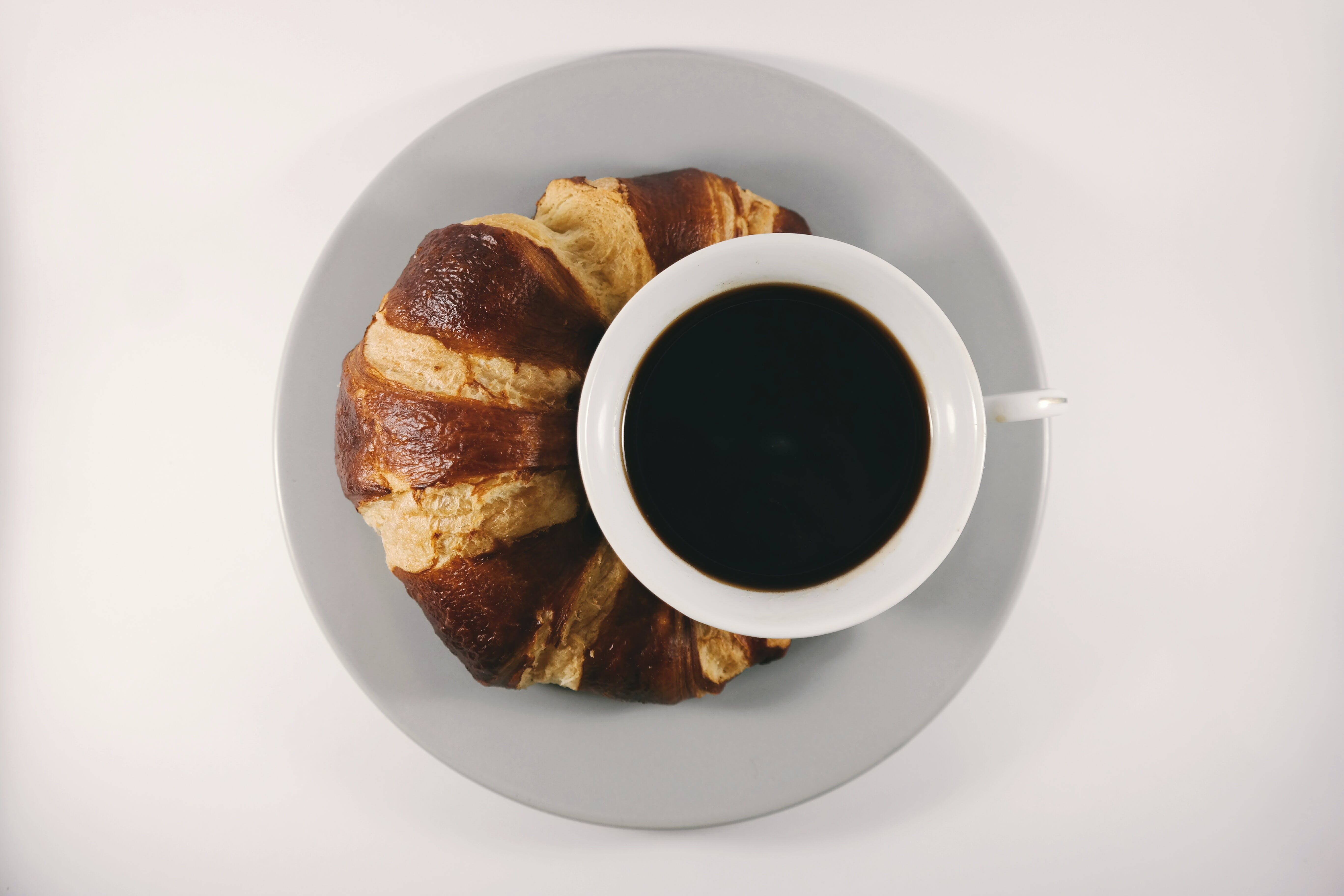 Croissant on Ceramic Plate Beside Cup With Coffee
