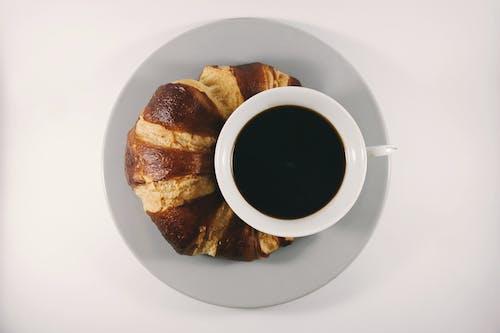 Kostenloses Stock Foto zu becher, croissant, essen, getränk