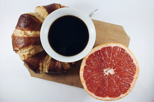 Black Coffee in Between Grapefruit and Croissant on Brown Wooden Board