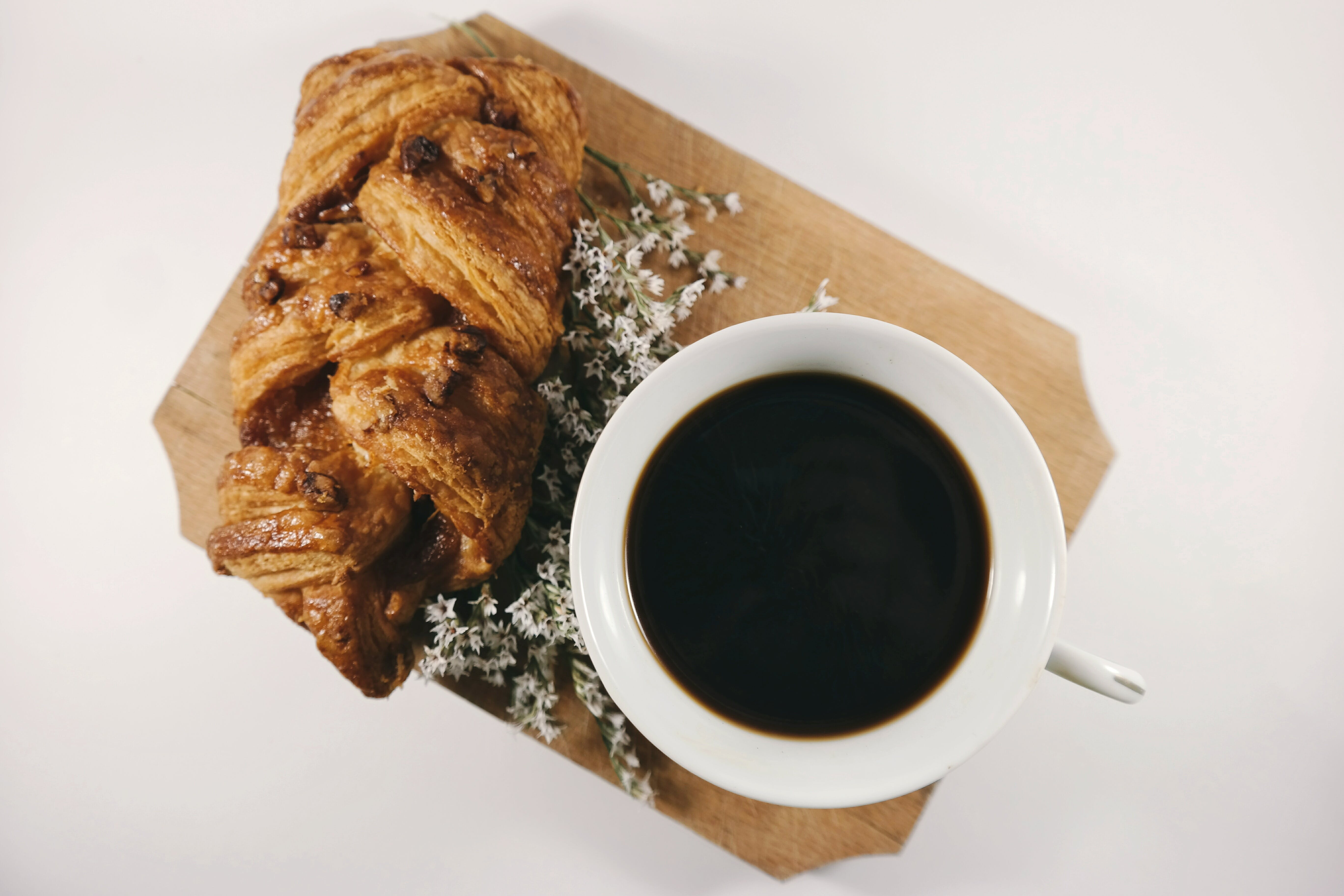 White Ceramic Teacup Filled With Coffee Near Baked Bread