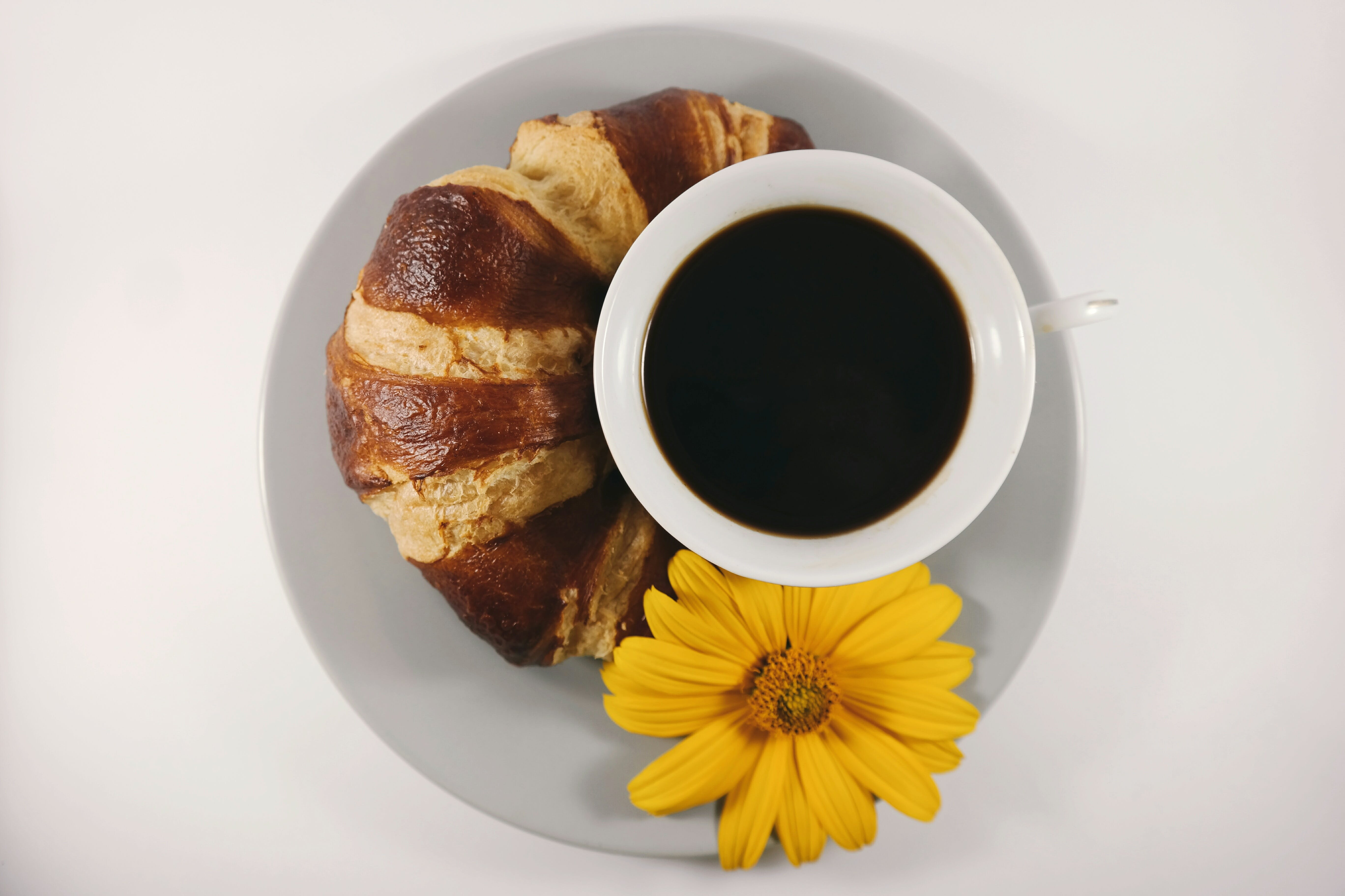 Cup of Coffee Beside Bread on Plate