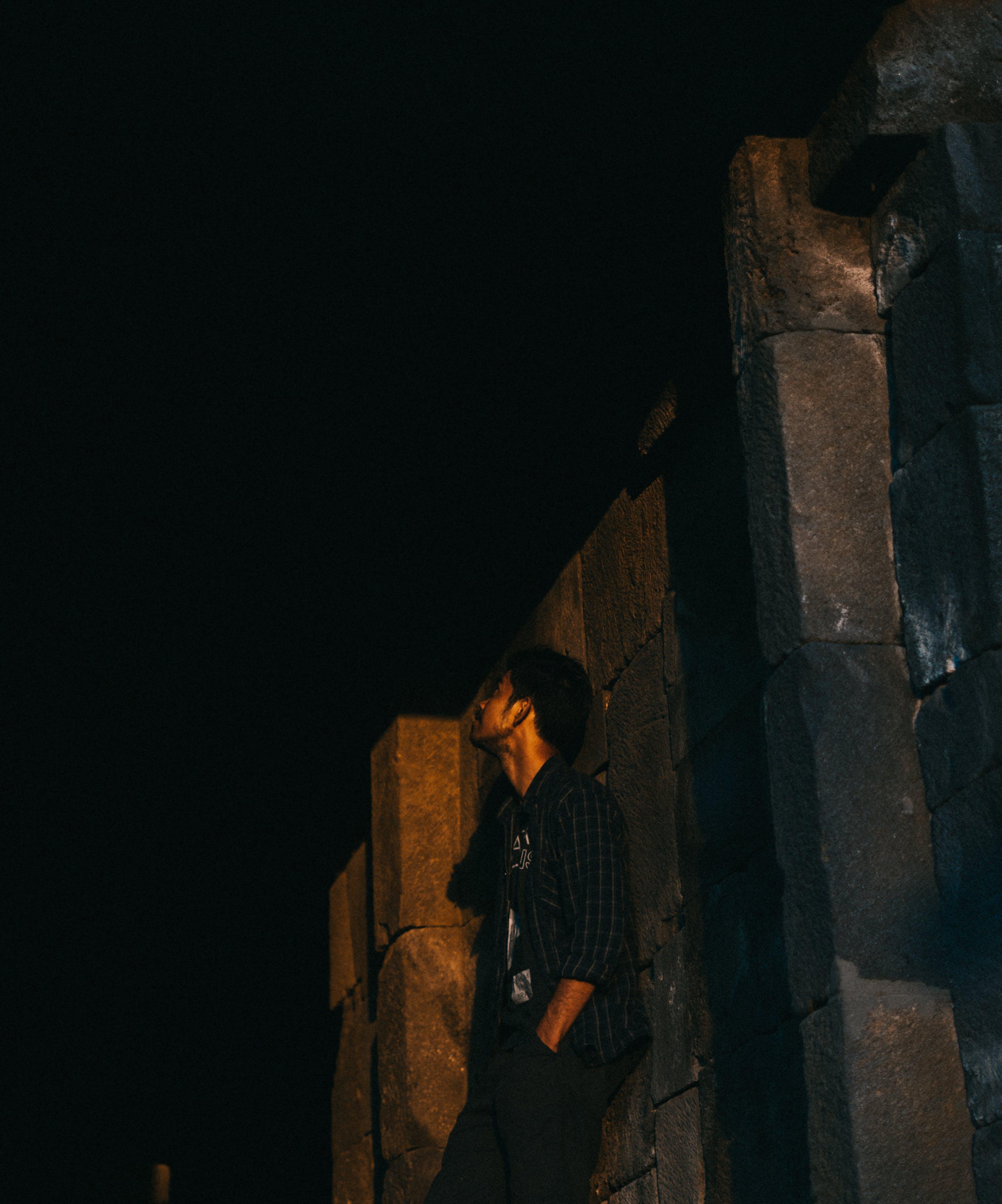 Foto profissional grátis de apoiando, homem, muro, noite