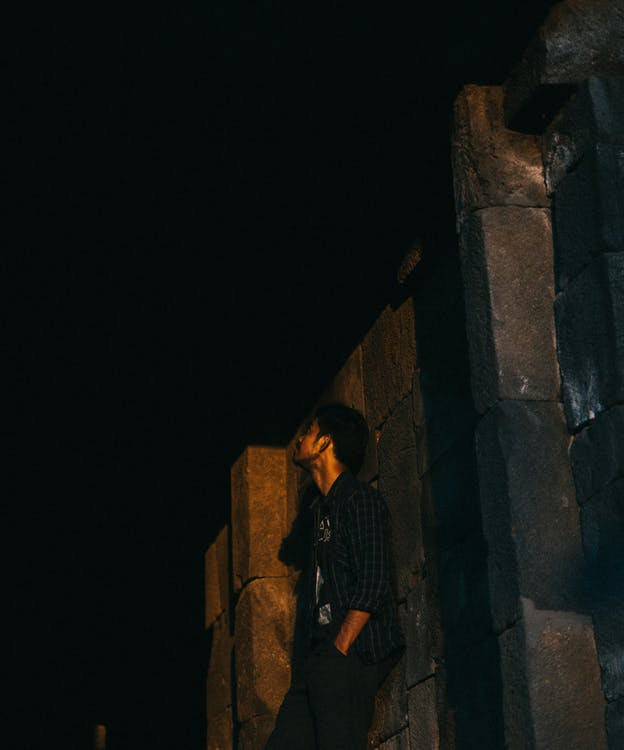 Photo of Man Leaning on Wall at Night-time