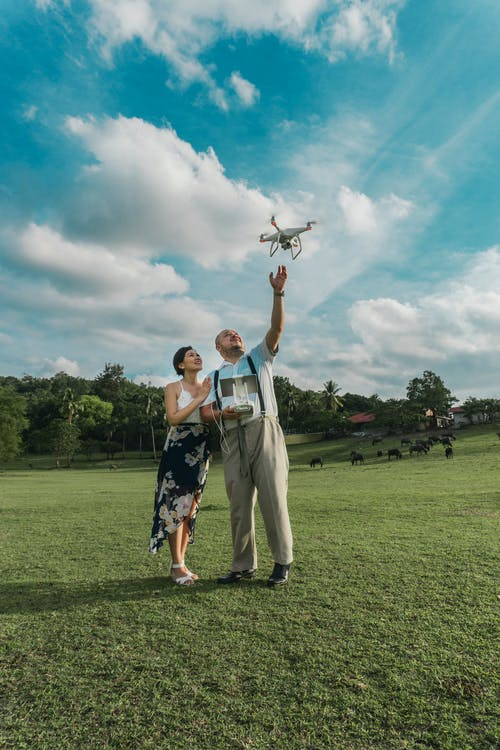 Man Standing Beside Woman Playing Drone