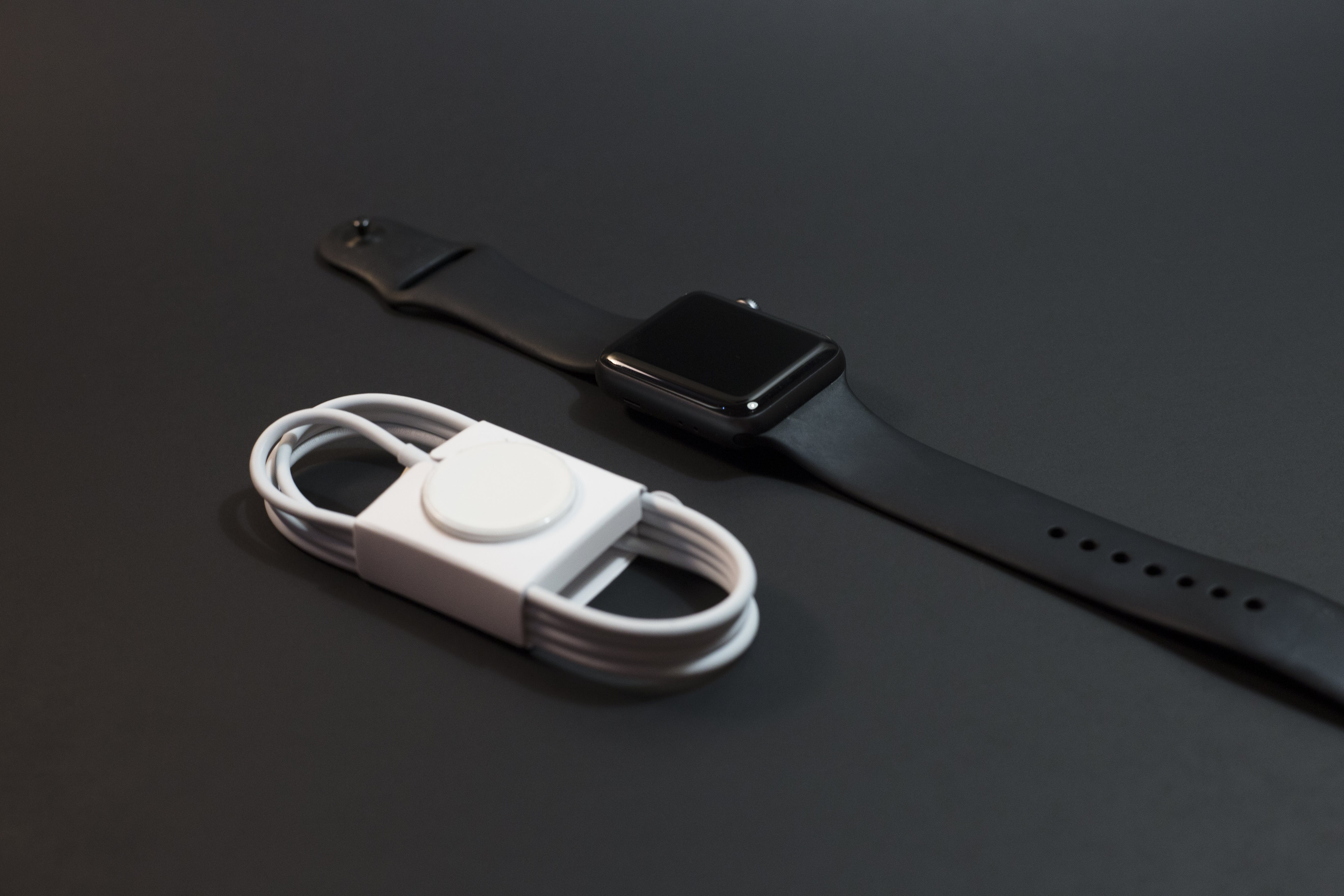 Black Aluminum Case Apple Watch With Sport Band Beside Magnetic Charger