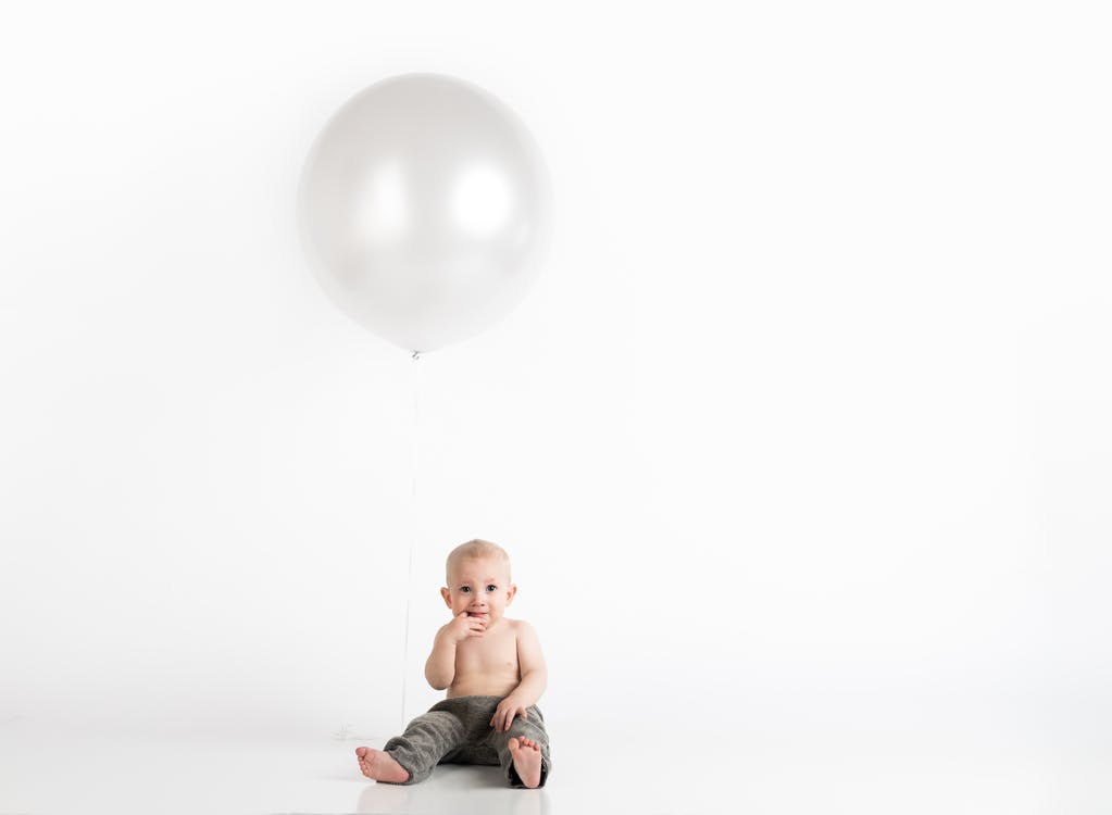 Baby Boy Sitting With White Inflatable Balloon Above