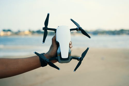 Person Holding White And Black Quadcopter Drone