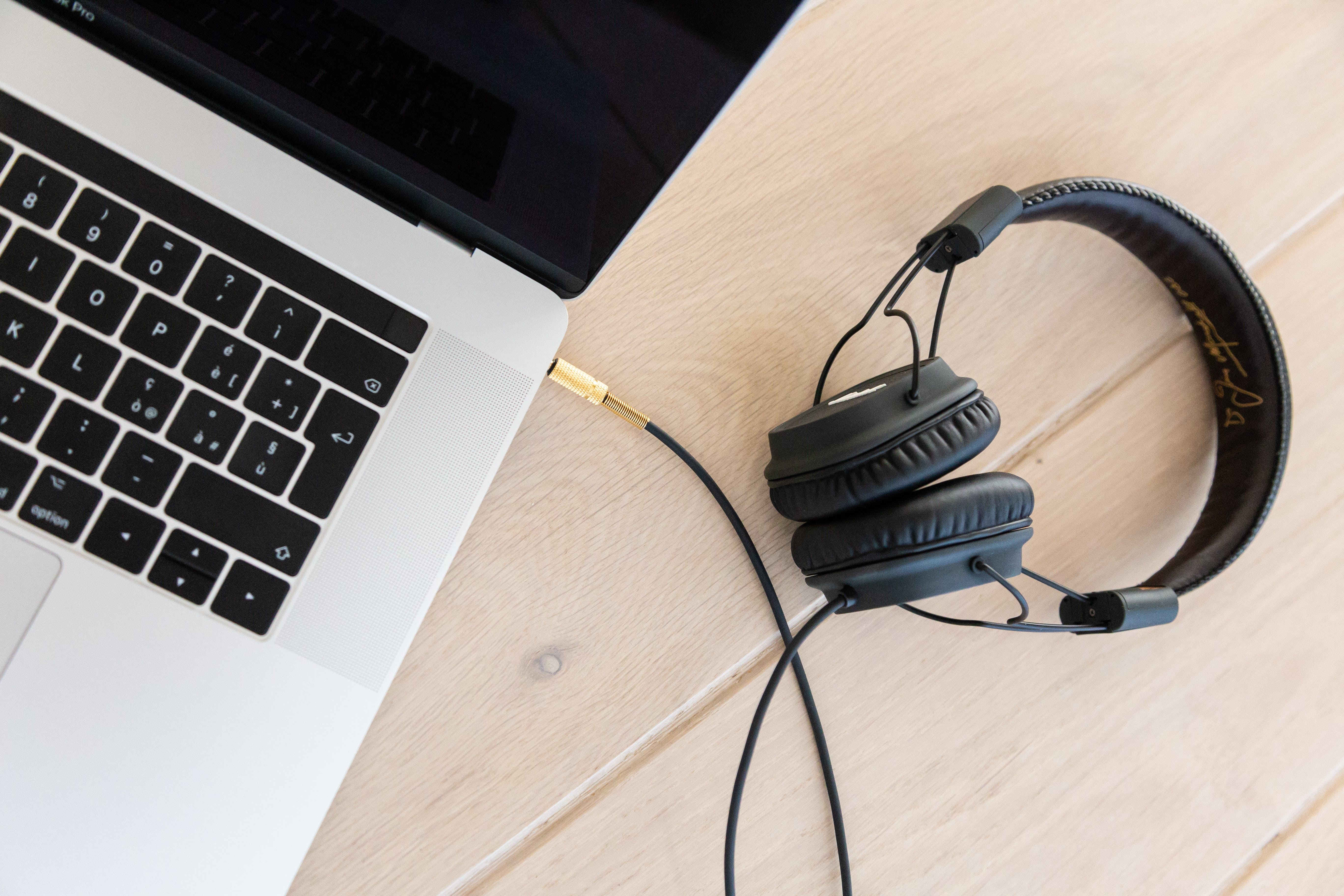 Black Corded Headphones Plugged in Macbook Pro on Brown Wooden Surface