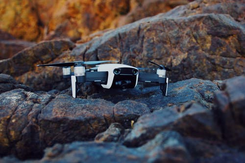 Shallow Focus Photography of White and Black Quadcopter Drone