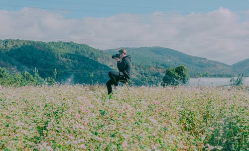 Man Sitting in the Middle of Flower Field Using Black Dslr Camera