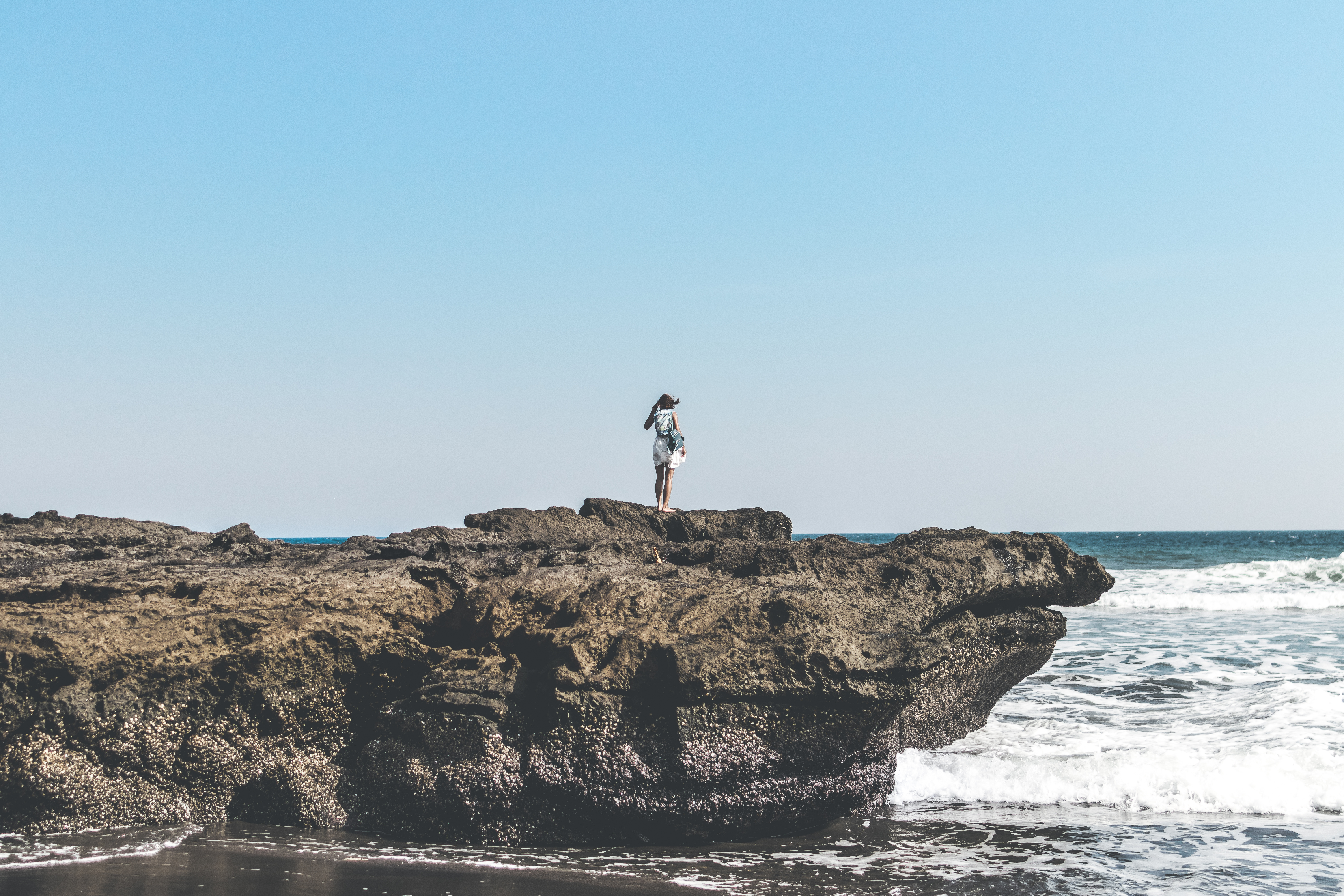Person Standing On A Rock Beside Seashore
