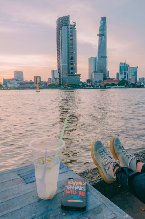 Person Sitting Beside Table Near Body of Water and Buildings