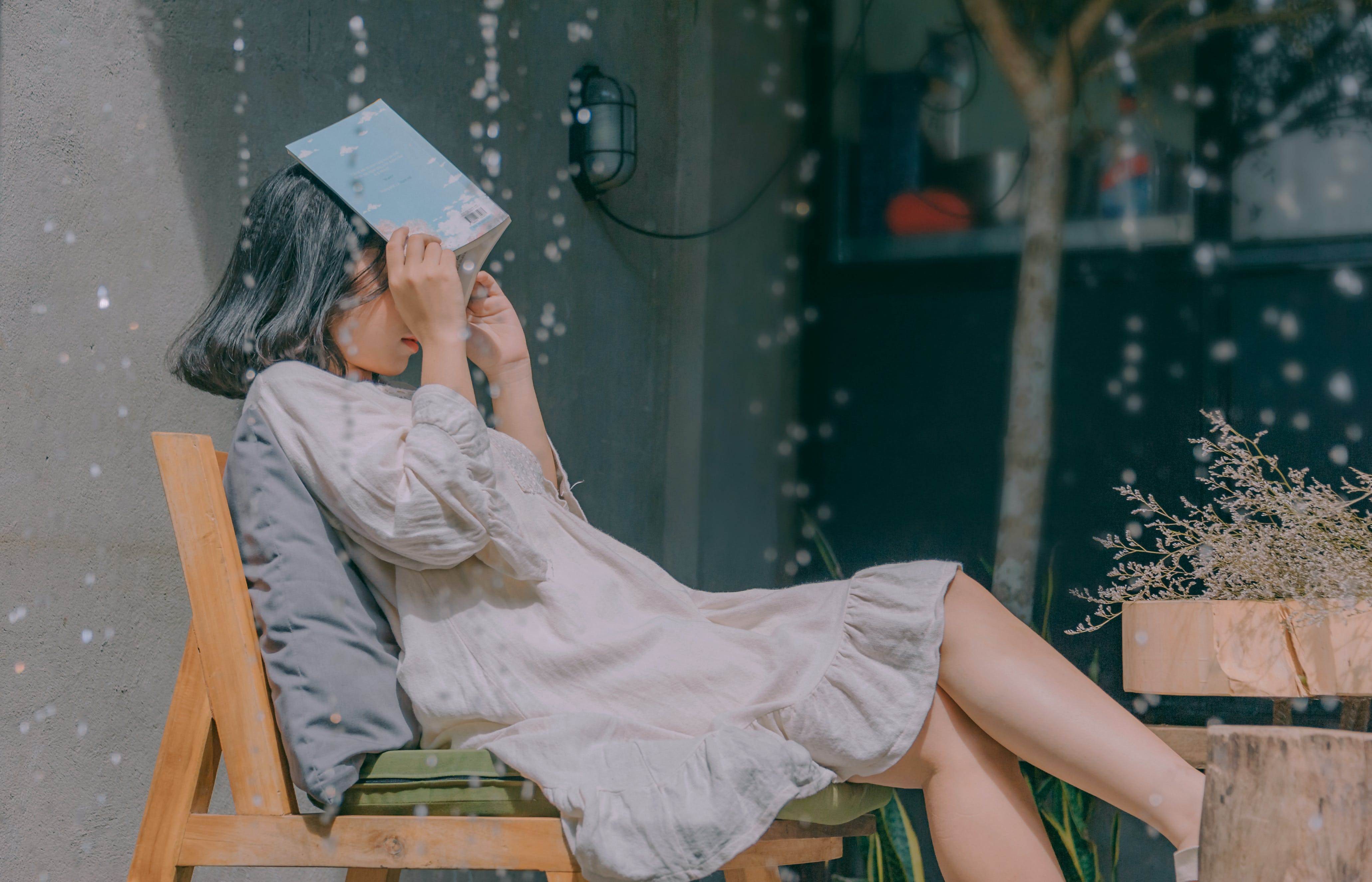 Woman Sitting on Chair While Holding Book