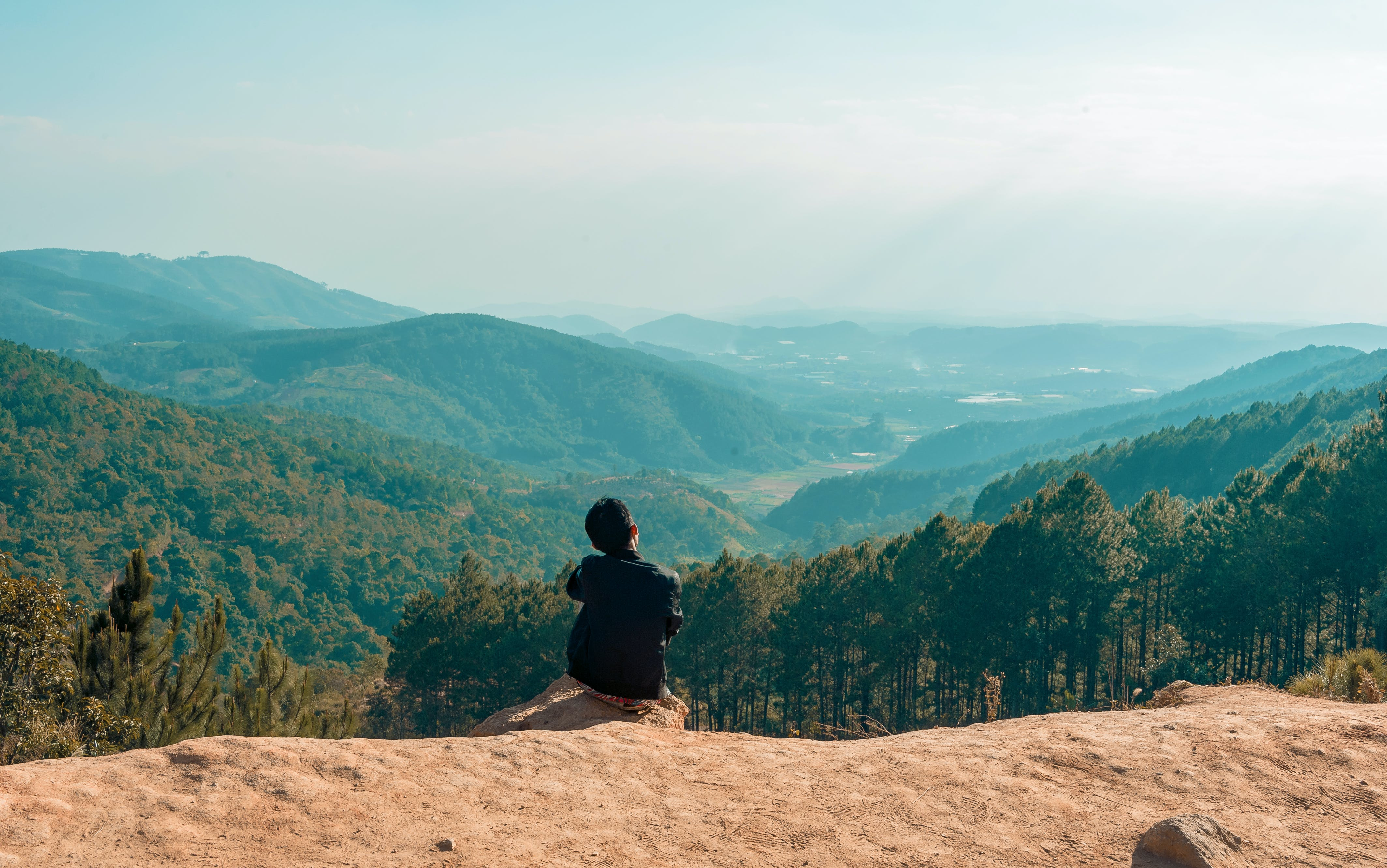 Man Sitting on Cliff Overlooking Mountain