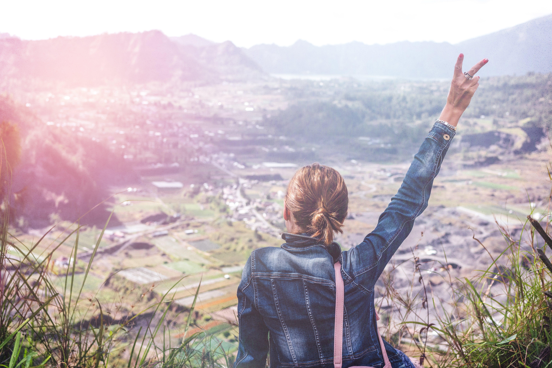 Woman in Denim Jacket Raising Her Hand