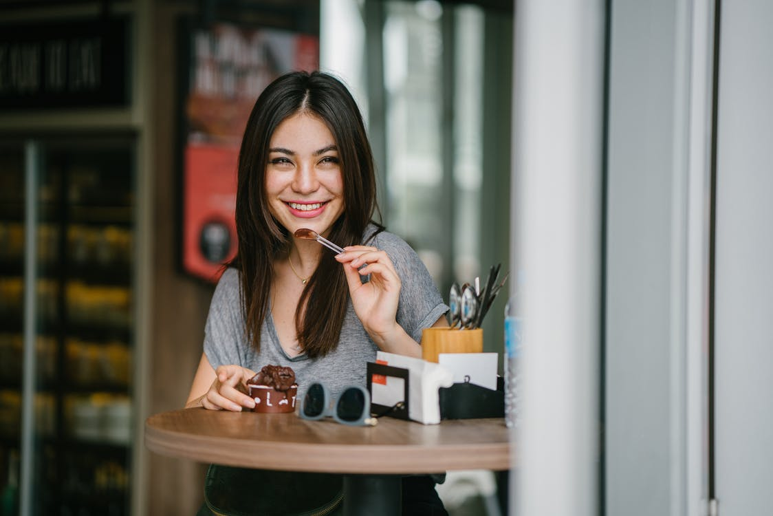 Woman Sitting at Table Holding Ice Cream
