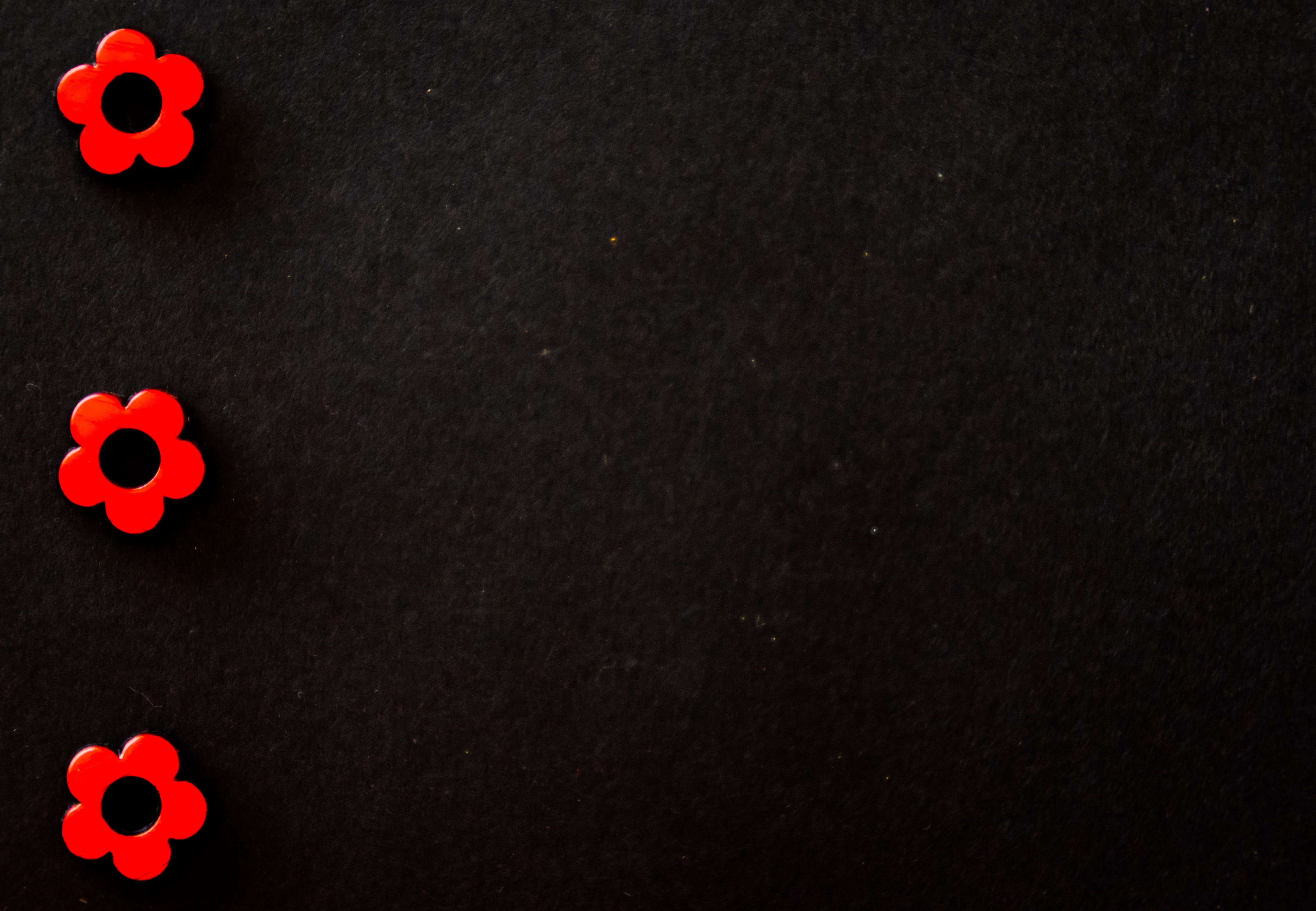 Three Red Flower Beads on Black Surface