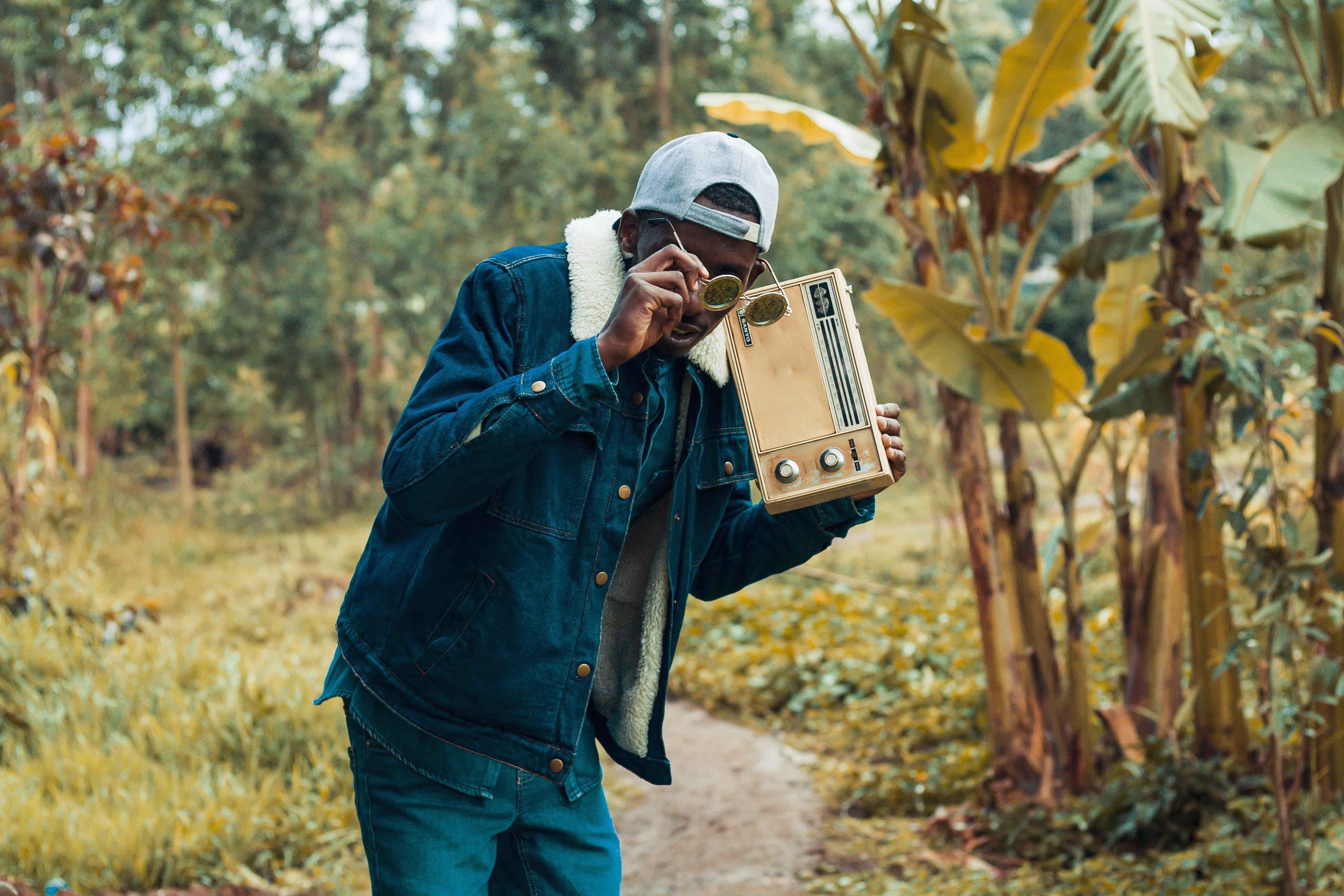 Man Holding Brown Boombox Radio