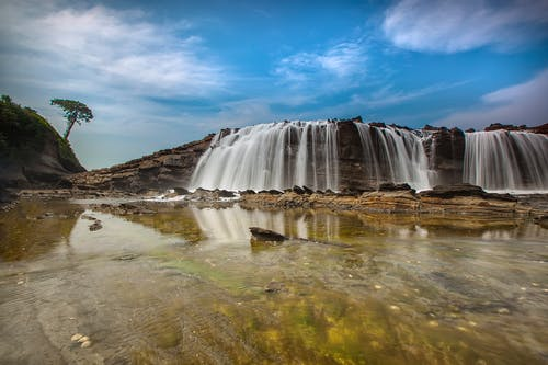 Waterfalls Near Hills Under Blue Sky and White Clouds