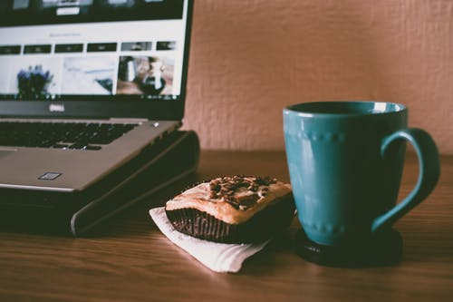 Blue Ceramic Mug Beside Cupcake