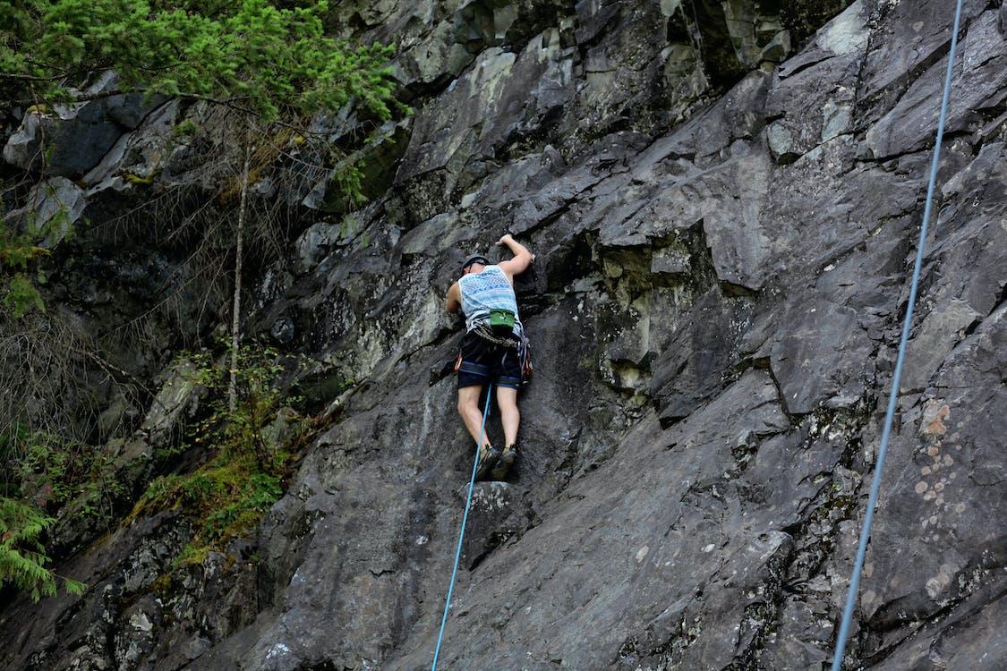 Man Climbing on Rocky Cliff