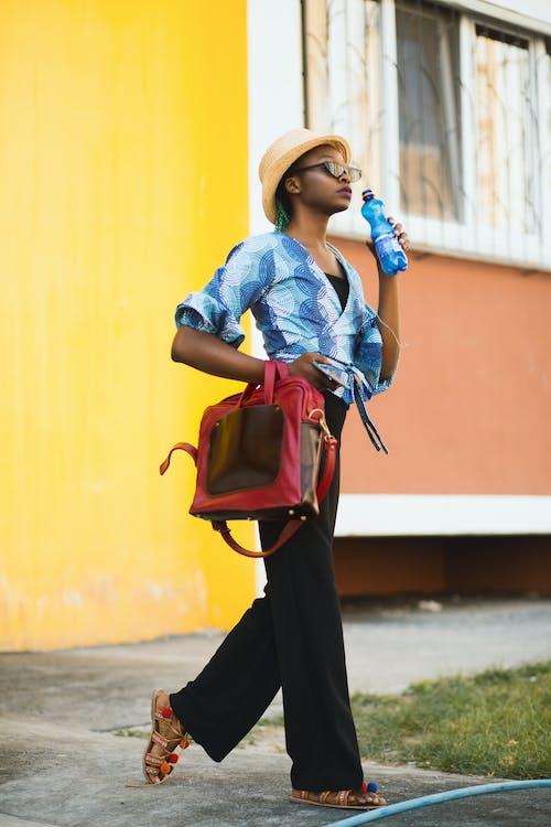 Mulher Com Blusa Azul Segurando Uma Garrafa Azul E Uma Sacola Vermelha De Duas Vias Ao Ar Livre